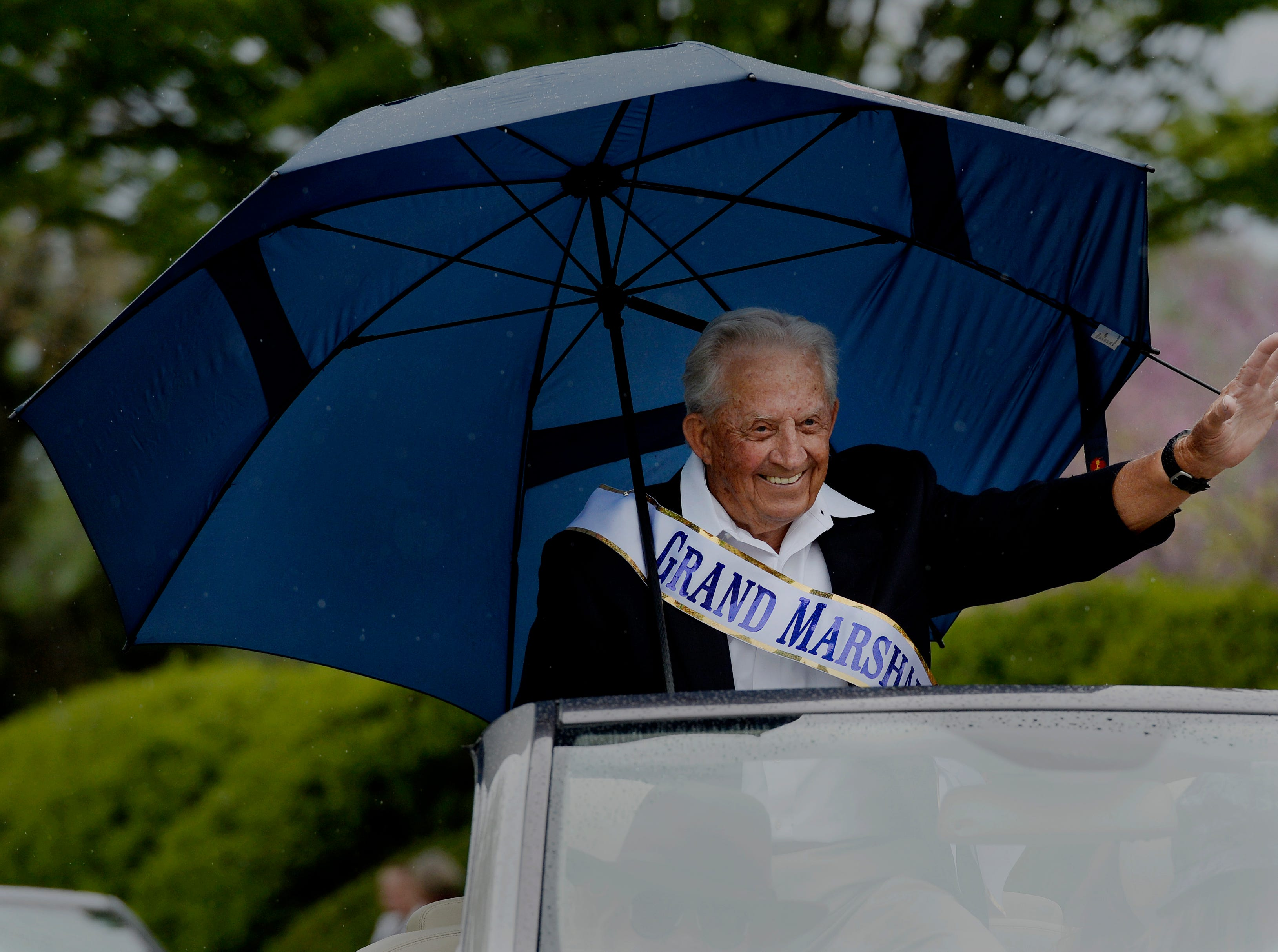 """Grand Marshal Jim Redd waves to the crowd during Brentwood's """"A Golden Gallop"""" parade celebrating its 50th year as a community on Saturday, April 13, 2019, in Brentwood, Tenn."""
