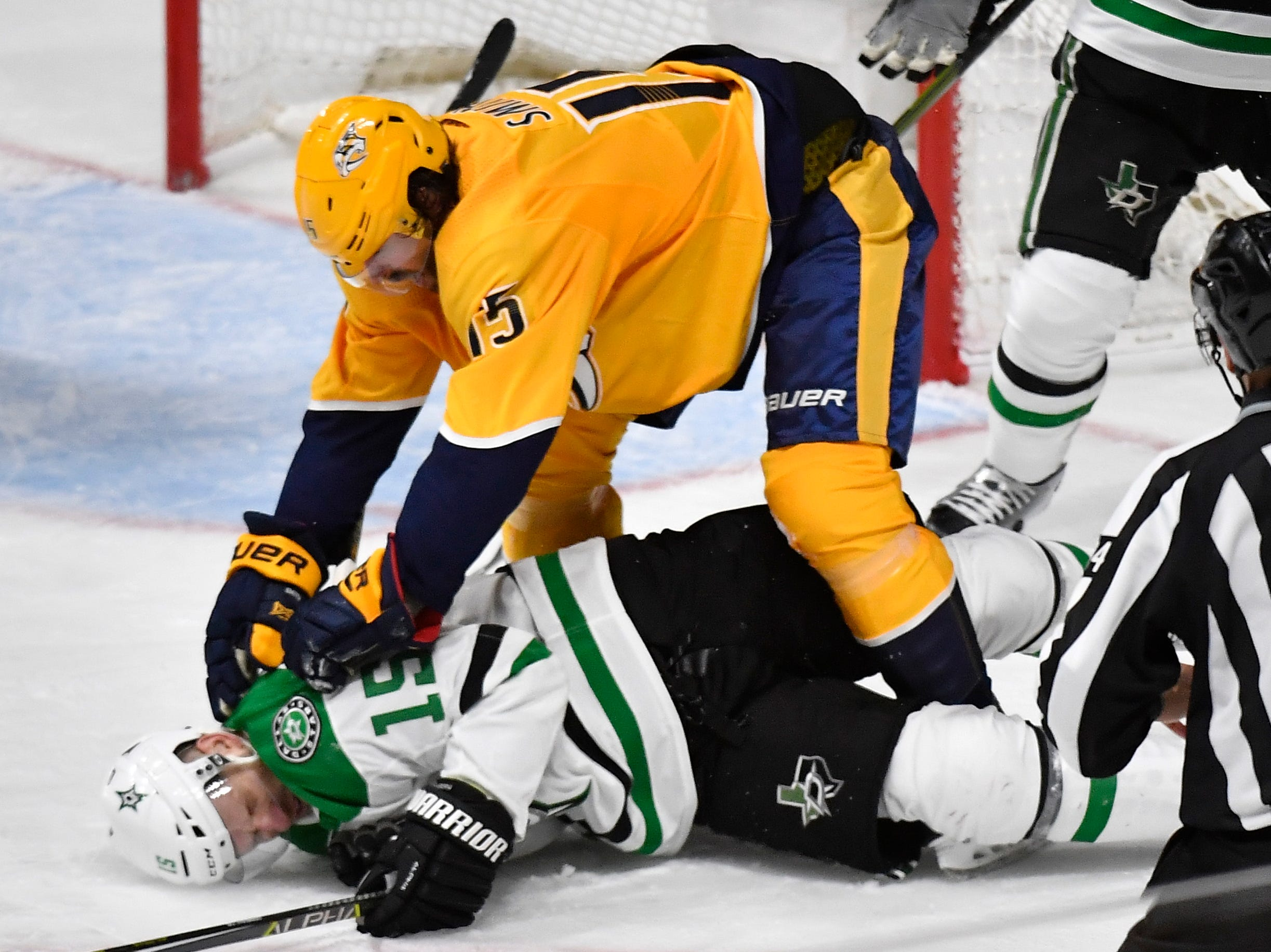 Nashville Predators right wing Craig Smith (15) pounds Dallas Stars left wing Blake Comeau (15) during the third period of the divisional semifinal game at Bridgestone Arena in Nashville, Tenn., Saturday, April 13, 2019.
