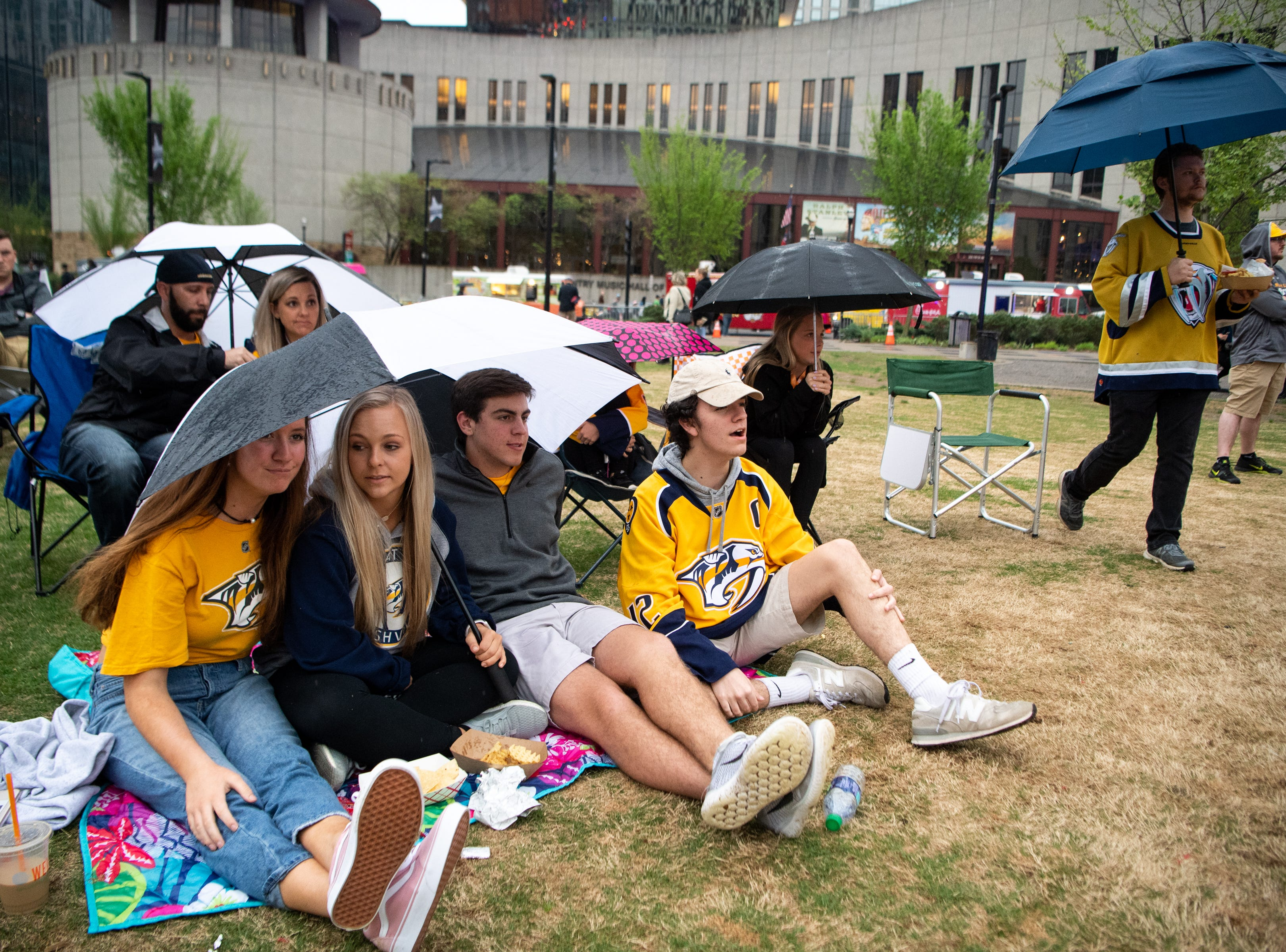 Fans share an umbrella during the second period of the Nashville Predators game against the Dallas Stars at Preds Party in the Park at Walk of Fame Park Saturday, April 13, 2019, in Nashville, Tenn.