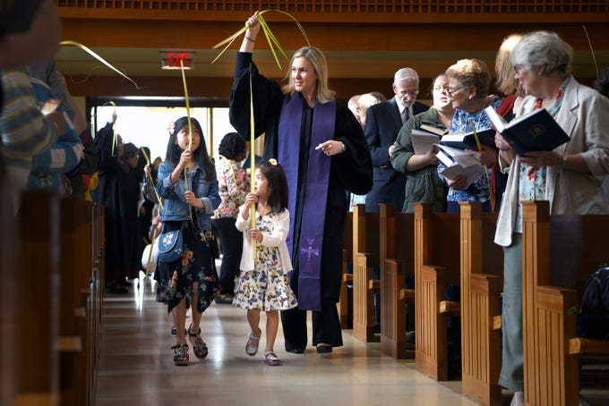 West Side Presbyterian Church in Ridgewood celebrates Palm Sunday on April 14, 2019. Rev. Penny Hogan and children of the congregation proceed into service waving palms.