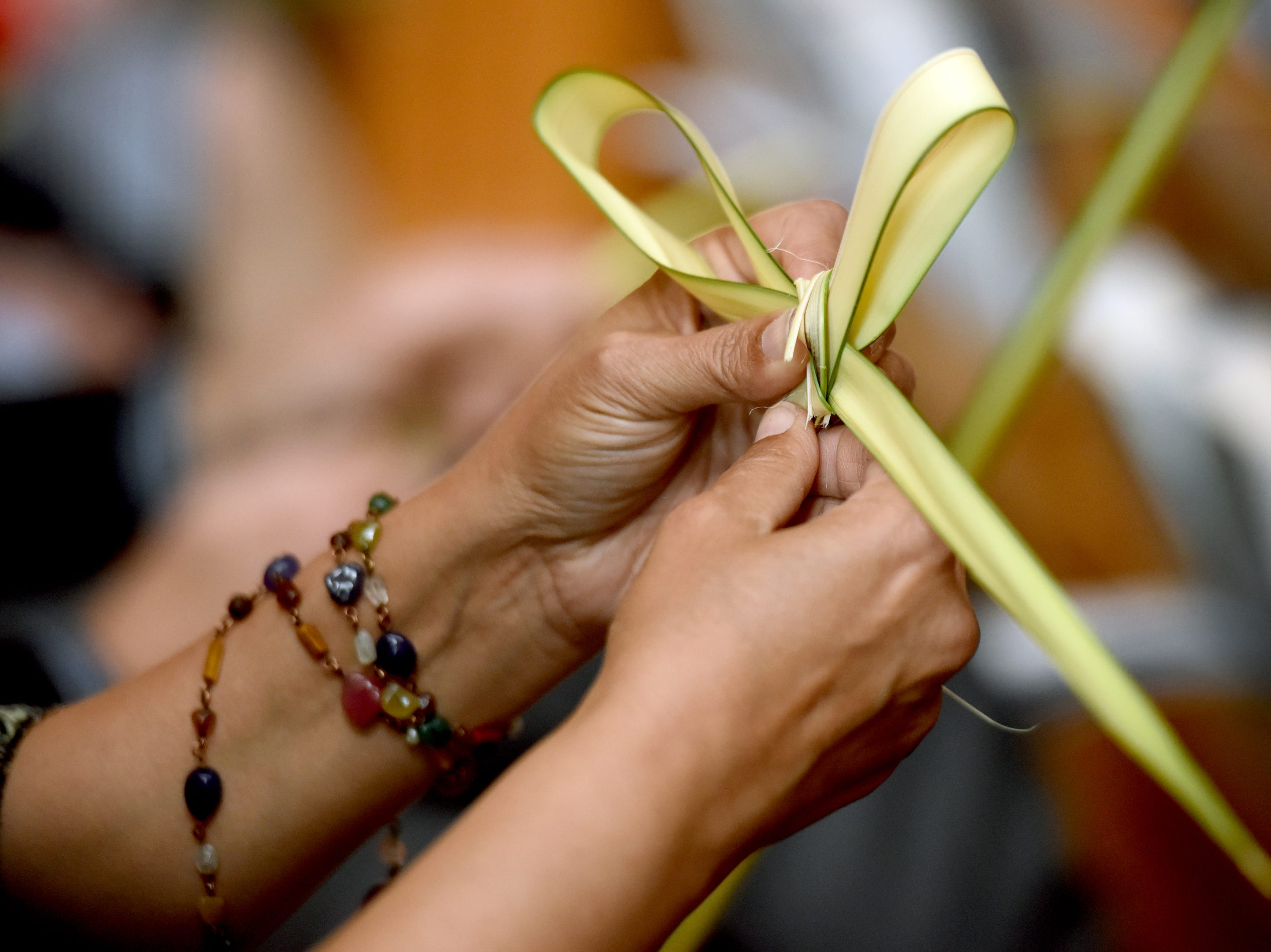 West Side Presbyterian Church in Ridgewood commemorated Palm Sunday on April 14, 2019 during services. A congregant makes a cross out of her palm.