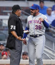 New York Mets manager Mickey Callaway, right, reacts after being ejected by home plate umpire Alfonso Marquez during the first inning of the team's baseball game against the Atlanta Braves on Saturday, April 13, 2019, in Atlanta.