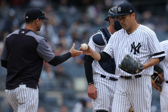 Apr 14, 2019; Bronx, NY, USA; New York Yankees starting pitcher Masahiro Tanaka (19) hands the ball to manager Aaron Boone (17) after being relieved during the fifth inning against the Chicago White Sox at Yankee Stadium.