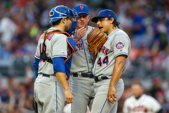 Apr 13, 2019; Atlanta, GA, USA; New York Mets catcher Travis d'Arnaud (18) and pitching coach Dave Eiland (58) and starting pitcher Jason Vargas (44) talk on the mound against the Atlanta Braves in the first inning at SunTrust Park.