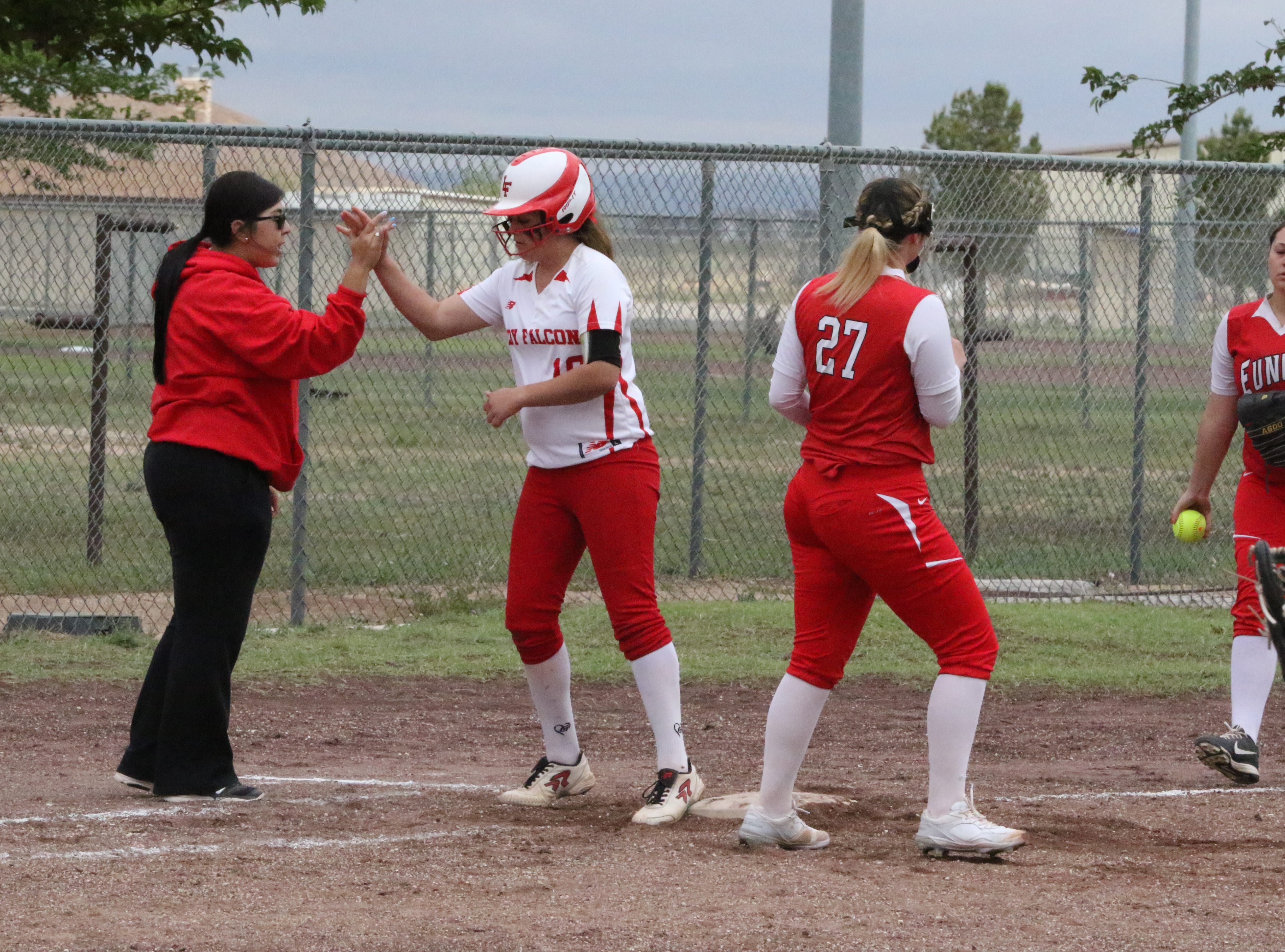 Faith McDonald high-fives coach  Kendra Granado after hitting a triple in Game 1 of Saturday's doubleheader.