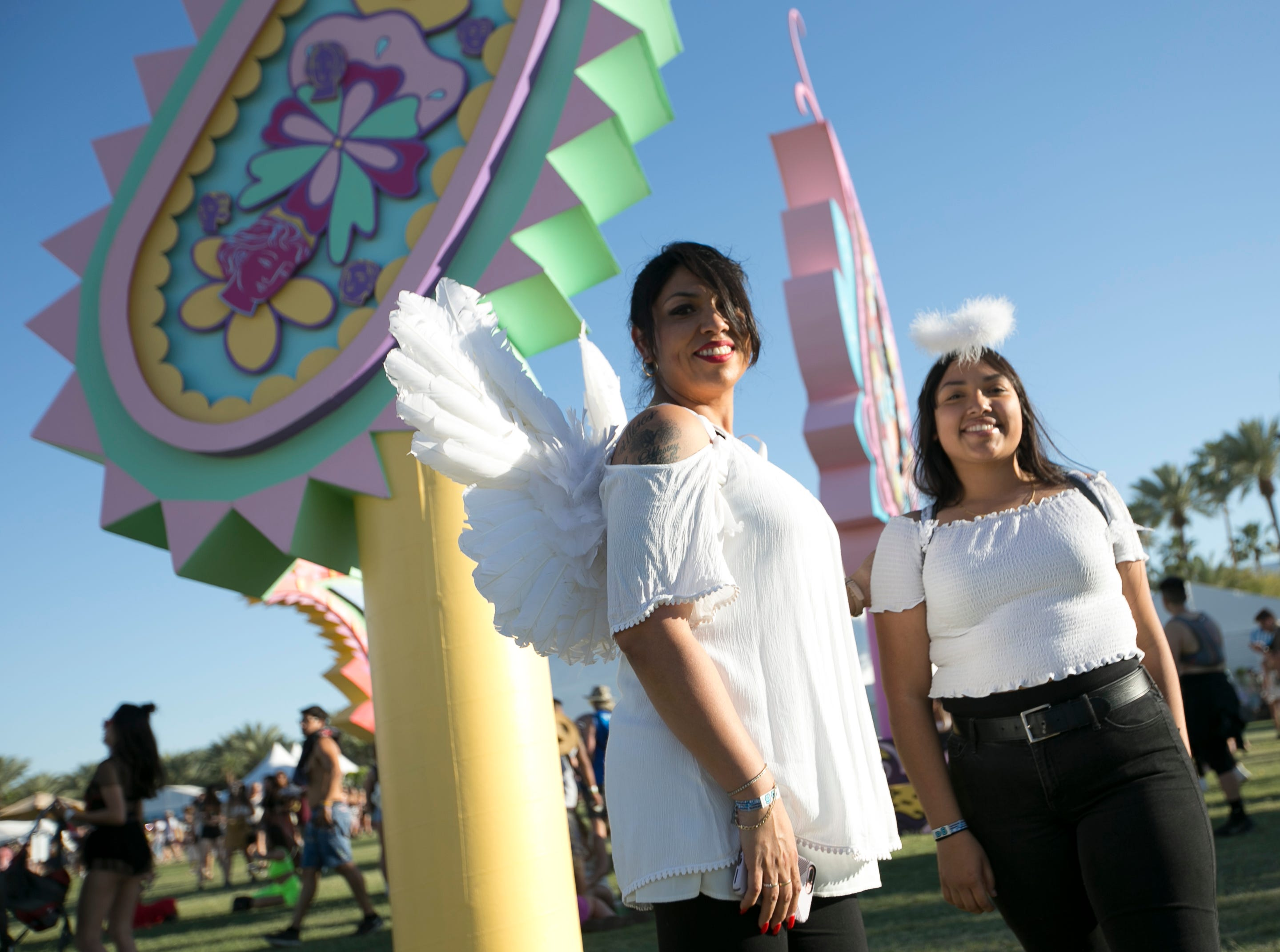Laura Alvarez (left) and Oddessey Bustamante (right) pose in front of an art installation at Coachella 2019 in Indio, Calif. on Sat. April 13, 2019.