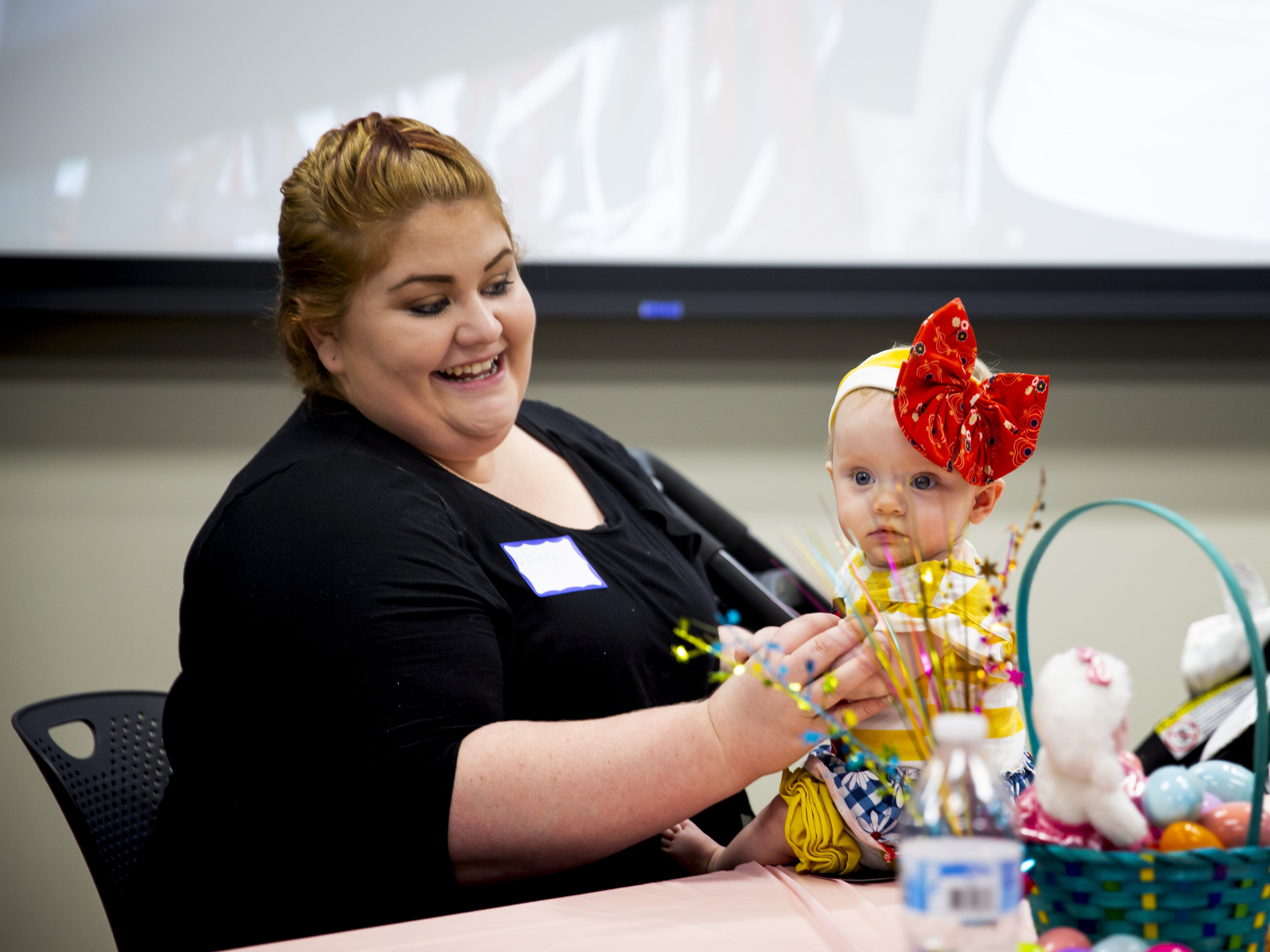 Brianna Jackson sets her 8-month-old daughter Aurora on a table at the Preemie NICU Reunion at Banner University Medical Center on April 13, 2019.