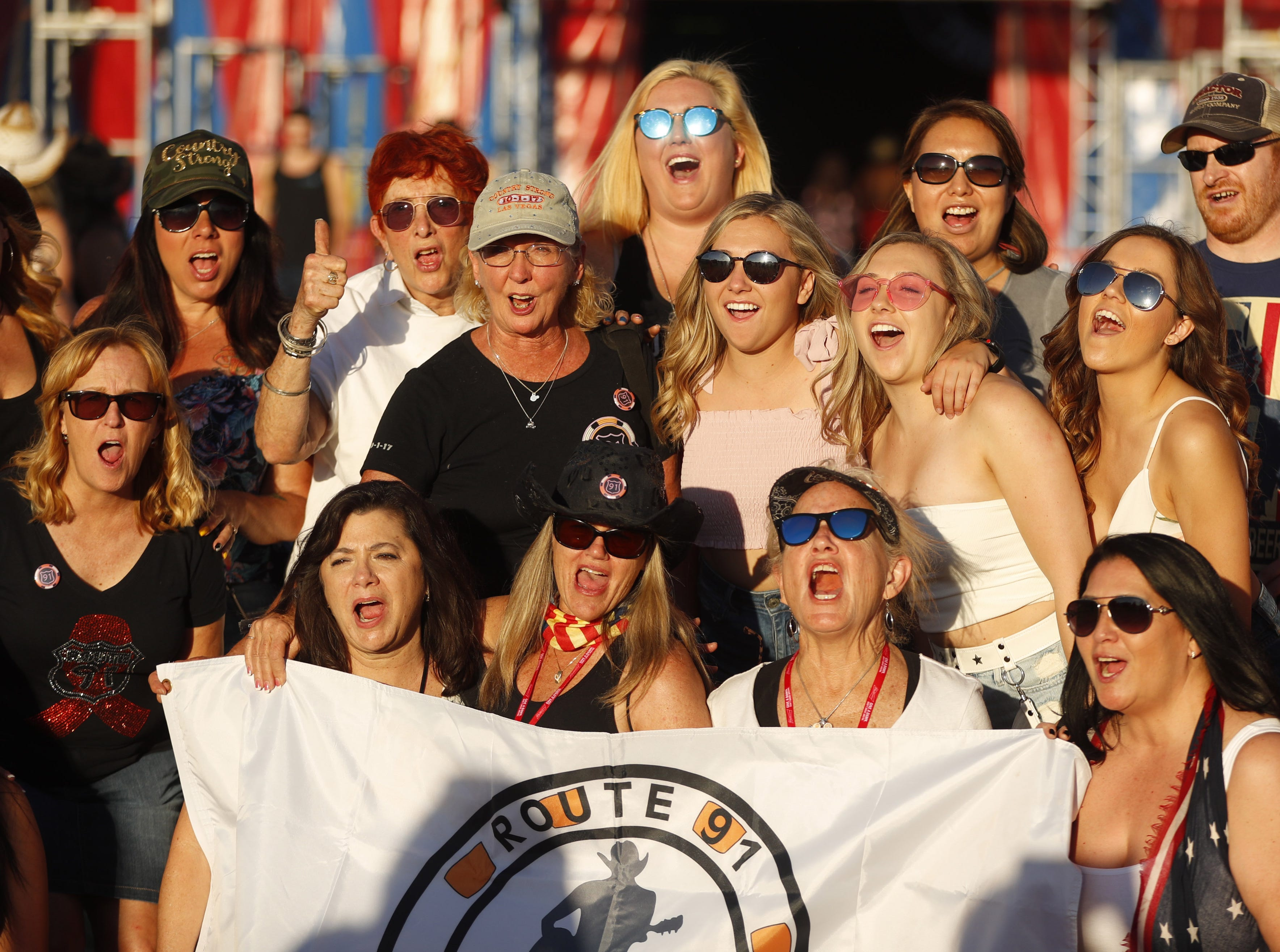 """Survivors of the Route 91 Harvest Festival shooting in Las Vegas yell """"country strong"""" for pictures during Country Thunder in Florence, Arizona, on April 13, 2019."""