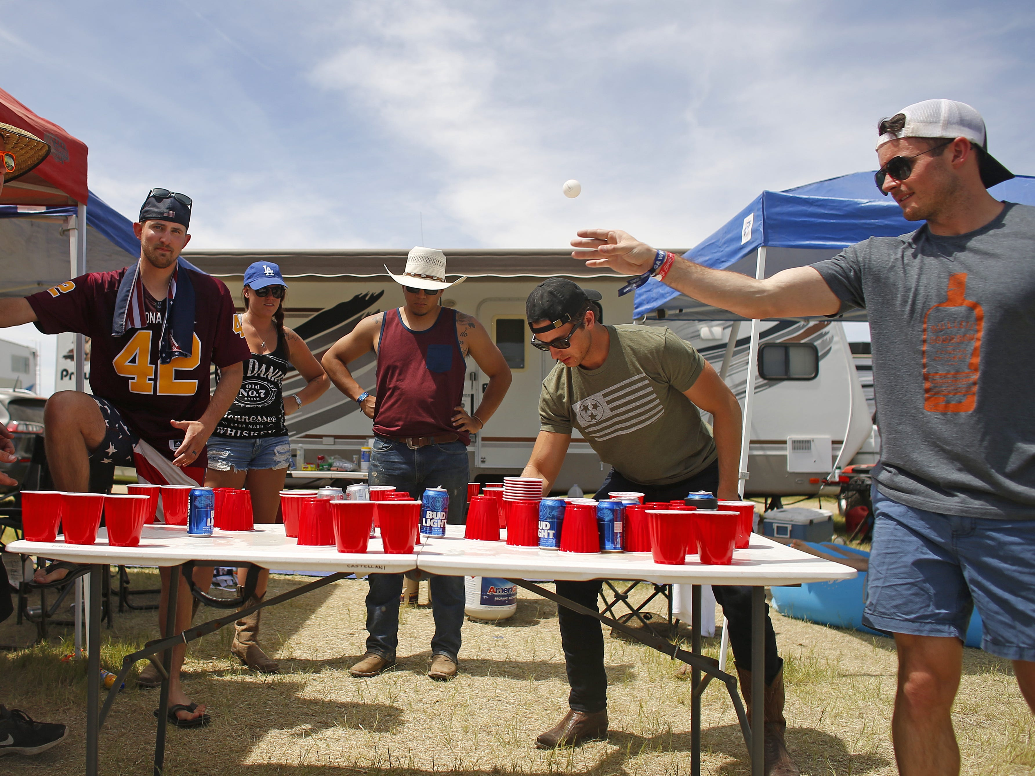 Clayton Boer (right) throws toward his teammate Ryan O'Halloran (left) while they play a drinking game called Dirt Cup during Country Thunder in Florence, Ariz. on Sunday, April 14, 2019.