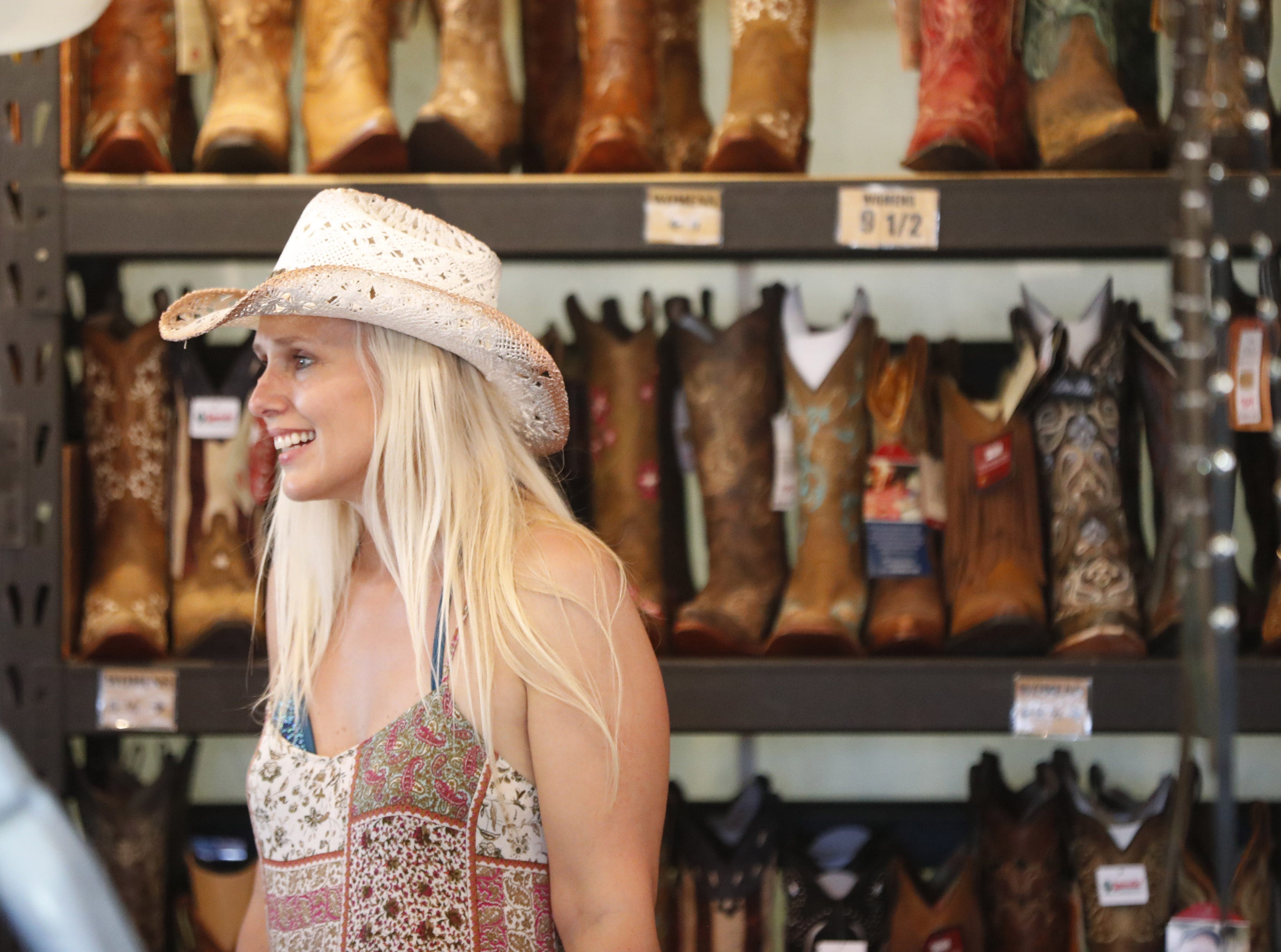 Country music fans look through boots for sale during Country Thunder in Florence, Ariz. on Saturday, April 13, 2019.