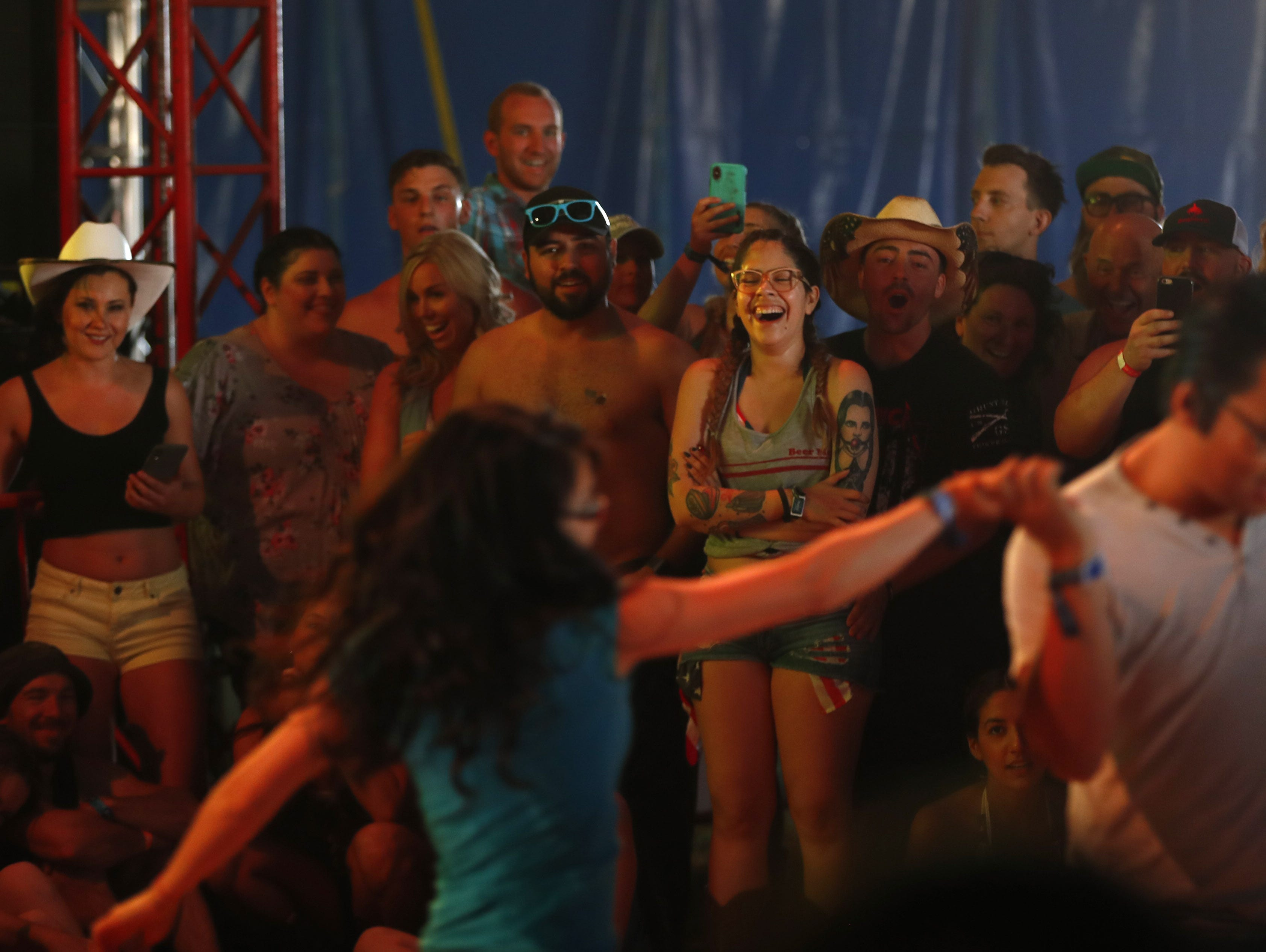 People laugh and clap for Christine Sanchez and Kennedy Wong as they dance during the finals of Dancing with the Thunder competition inside the Electric Thunder tent during Country Thunder in Florence, Ariz. on Saturday, April 13, 2019.