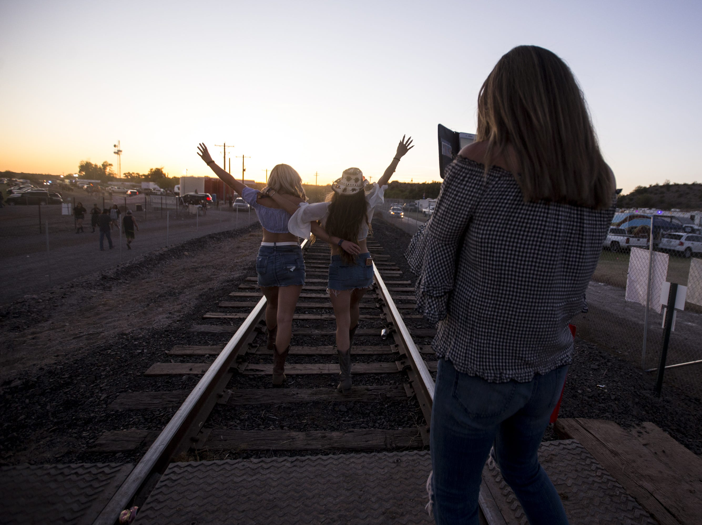 Hortencia Reyes takes a photo of Ashley Holland (left) and JonElle Reyes on April 13, 2019, during Day 3 of Country Thunder Arizona in Florence, Arizona.