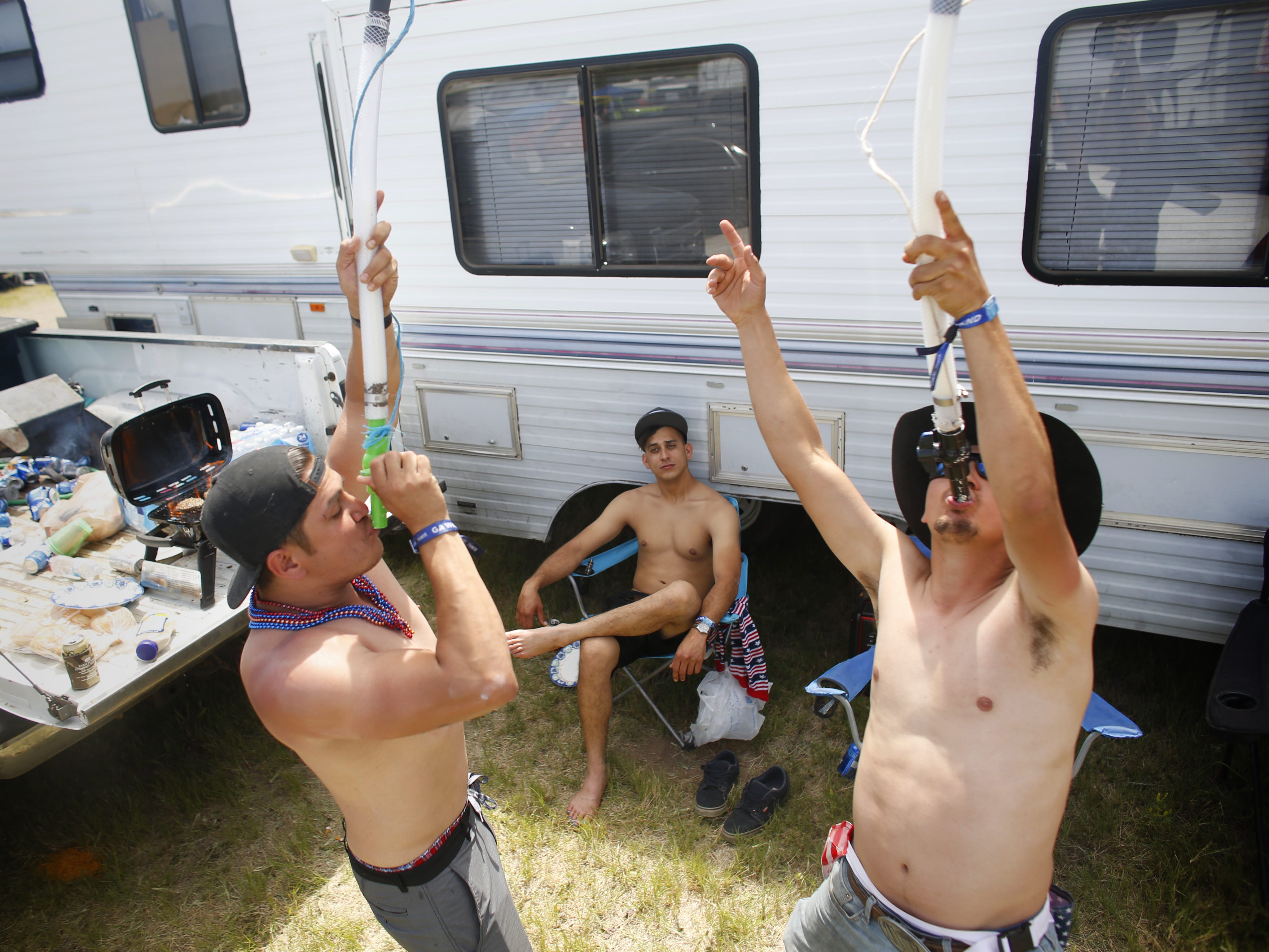 Max Pena (right) and his friend Brian Schurz (left) drink Bud Light from their beer bongs as Kenny Ramos watches during Country Thunder in Florence, Ariz. on Sunday, April 14, 2019.