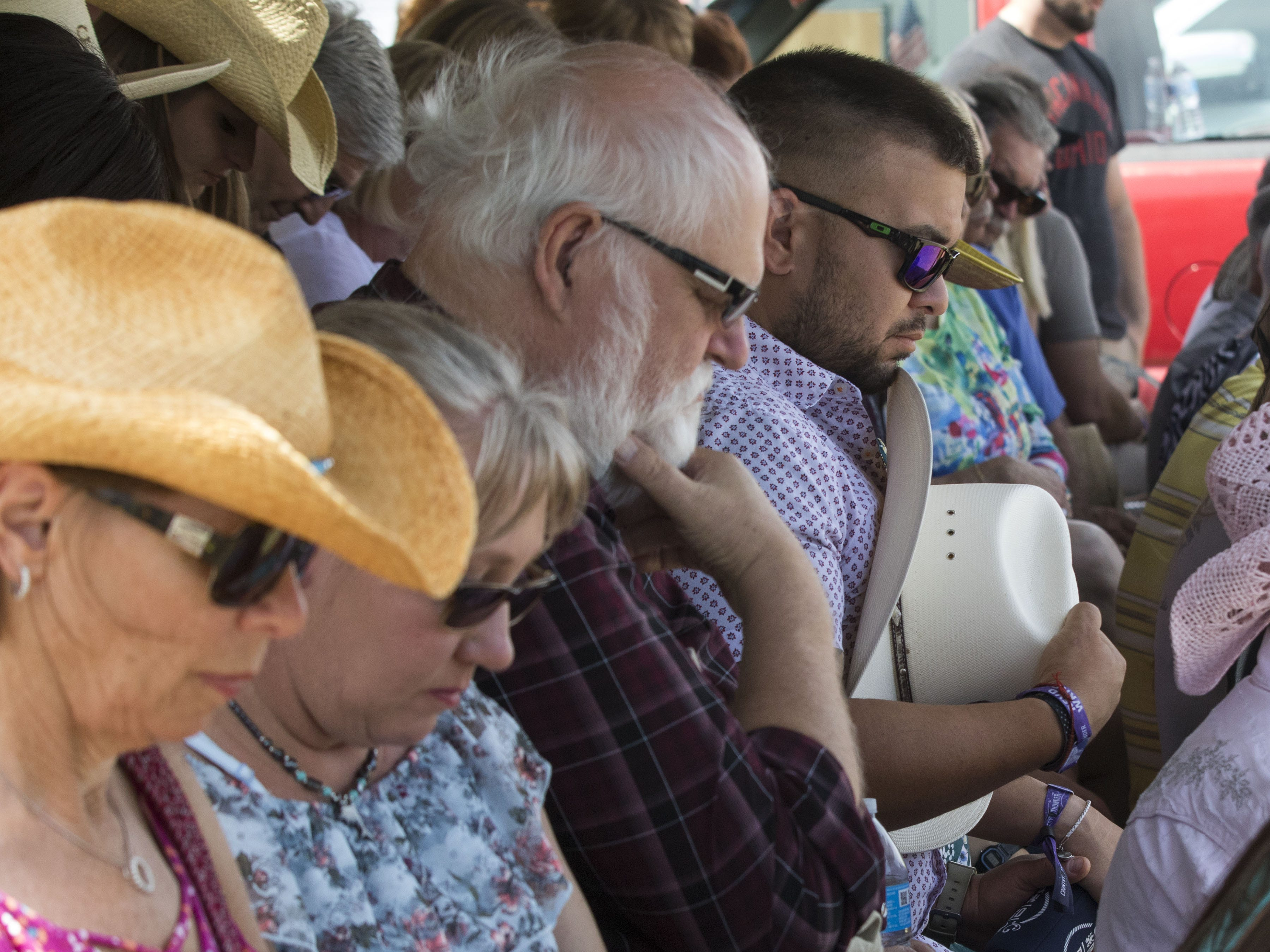 Church-goers bow their heads in prayer during Cowboy Church at Country Thunder Arizona on Sunday, April 14, 2019, in Florence, Arizona.