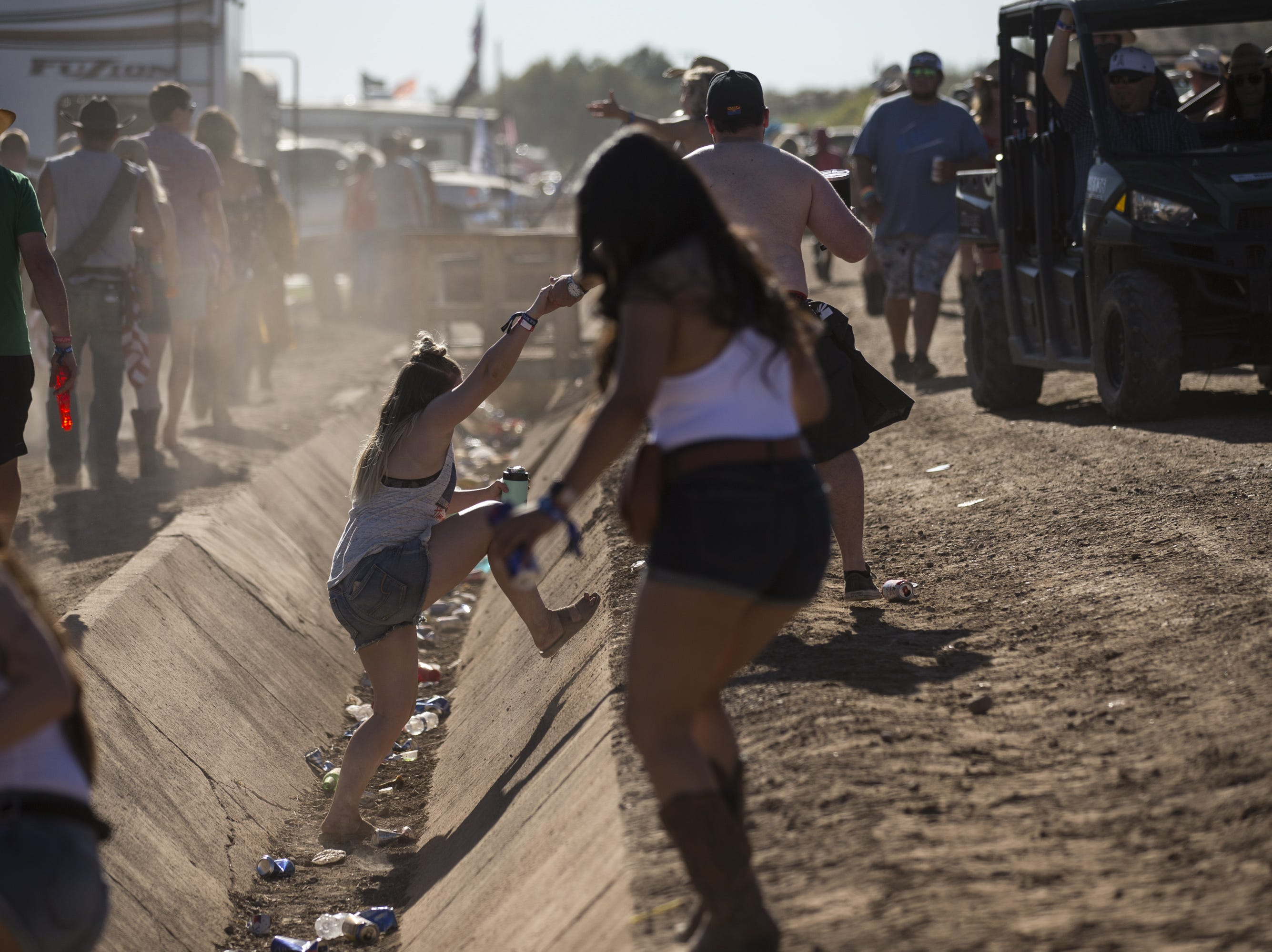 Festivalgoers cross a drainage ditch on Saturday, Apr. 13, 2019, during Day 3 of Country Thunder Arizona in Florence, Ariz.