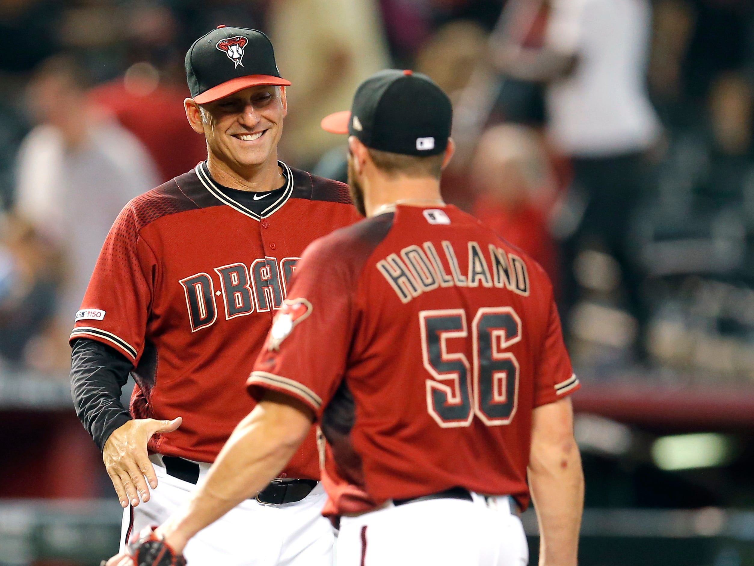 Arizona Diamondbacks manager Torey Lovullo, left, and Greg Holland (56) celebrate after defeating the San Diego Padres in a baseball game, Sunday, April 14, 2019, in Phoenix. (AP Photo/Rick Scuteri)
