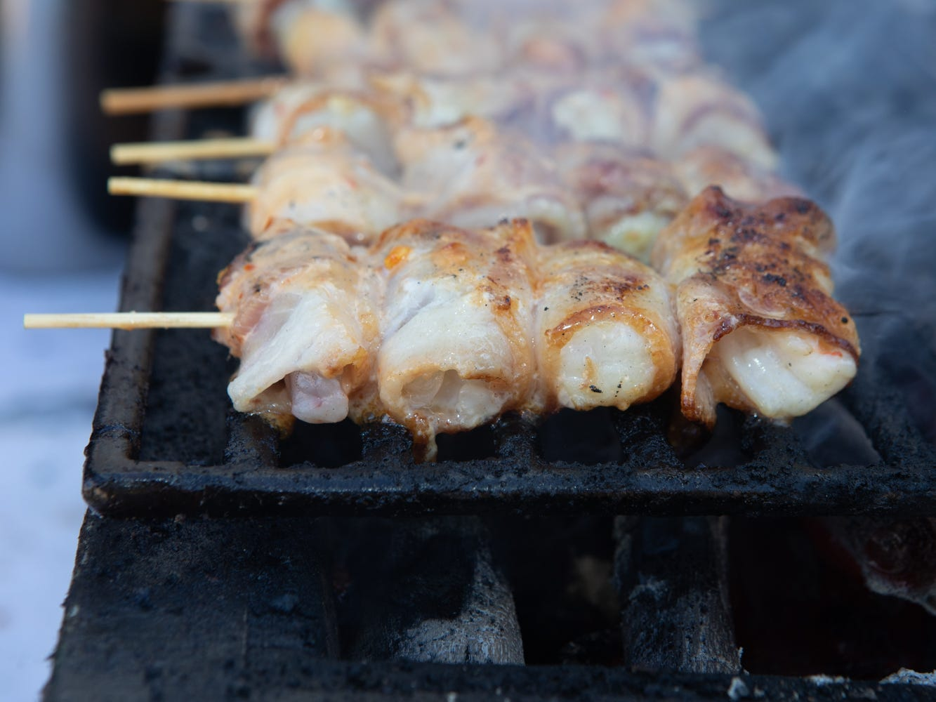 Bacon-wrapped shrimp skewers by Sushi Roku on the grill at the Scottsdale Culinary Festival on April 13, 2019.