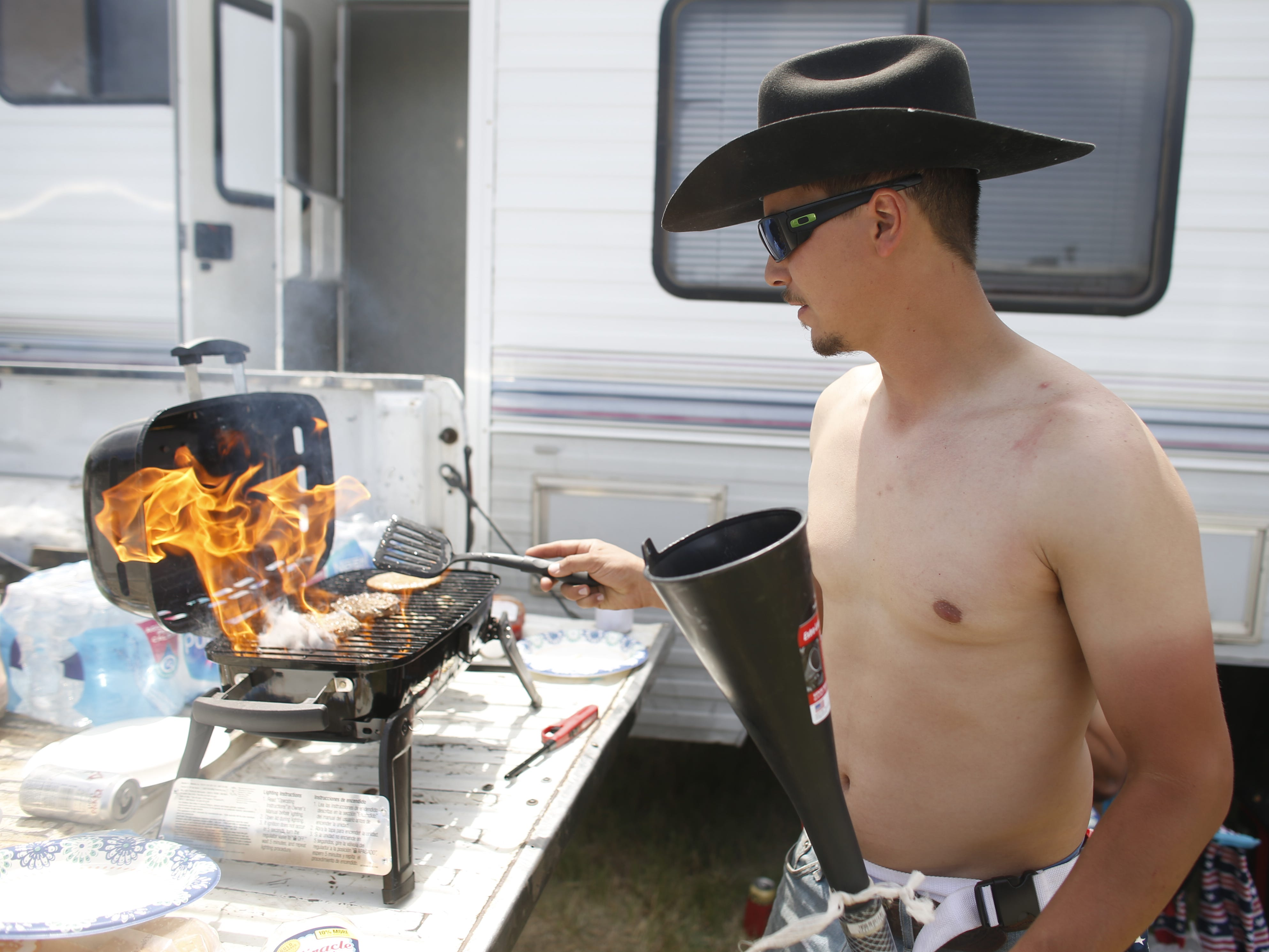 Max Pena grills some burgers for him and his friends outside their camper during Country Thunder in Florence, Ariz. on Sunday, April 14, 2019.