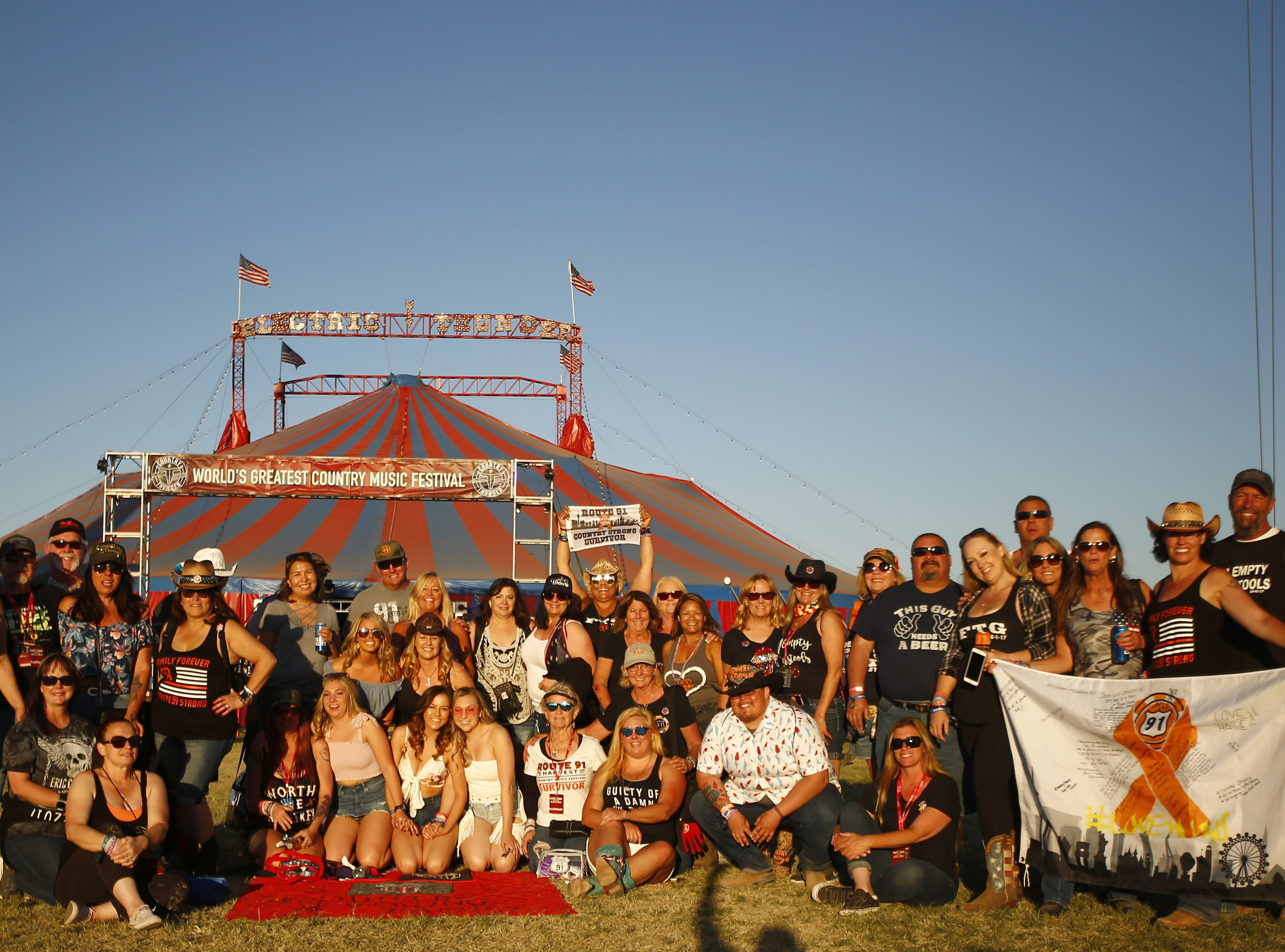Survivors of the Route 91 Harvest Festival shooting in Las Vegas gather around for pictures during Country Thunder in Florence, Arizona, on April 13, 2019.