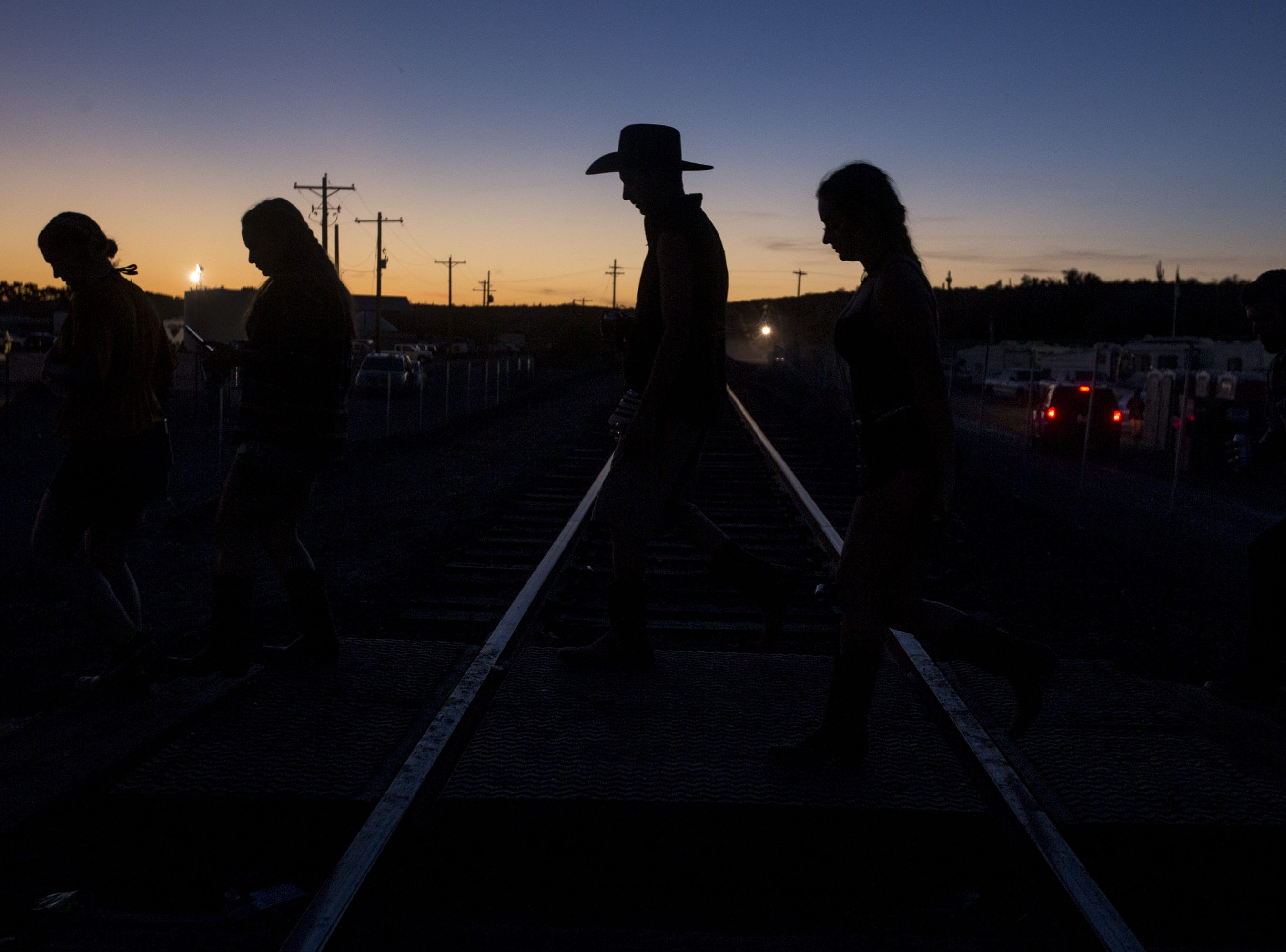 Festivalgoers cross train tracks on Saturday, April 13, 2019, during Day 3 of Country Thunder Arizona in Florence, Ariz.