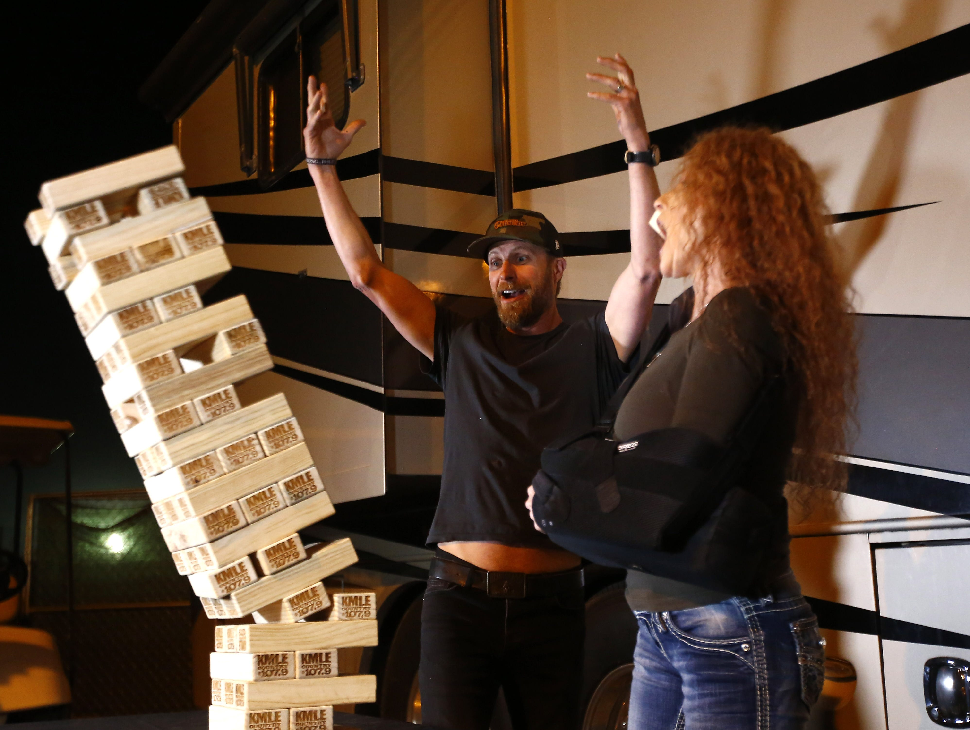 Dierks Bentley reacts as Lana Switzer pulls a block that causes the Jenga bricks to tumble at a KMLE event during Country Thunder in Florence, Arizona, on  April 13, 2019.