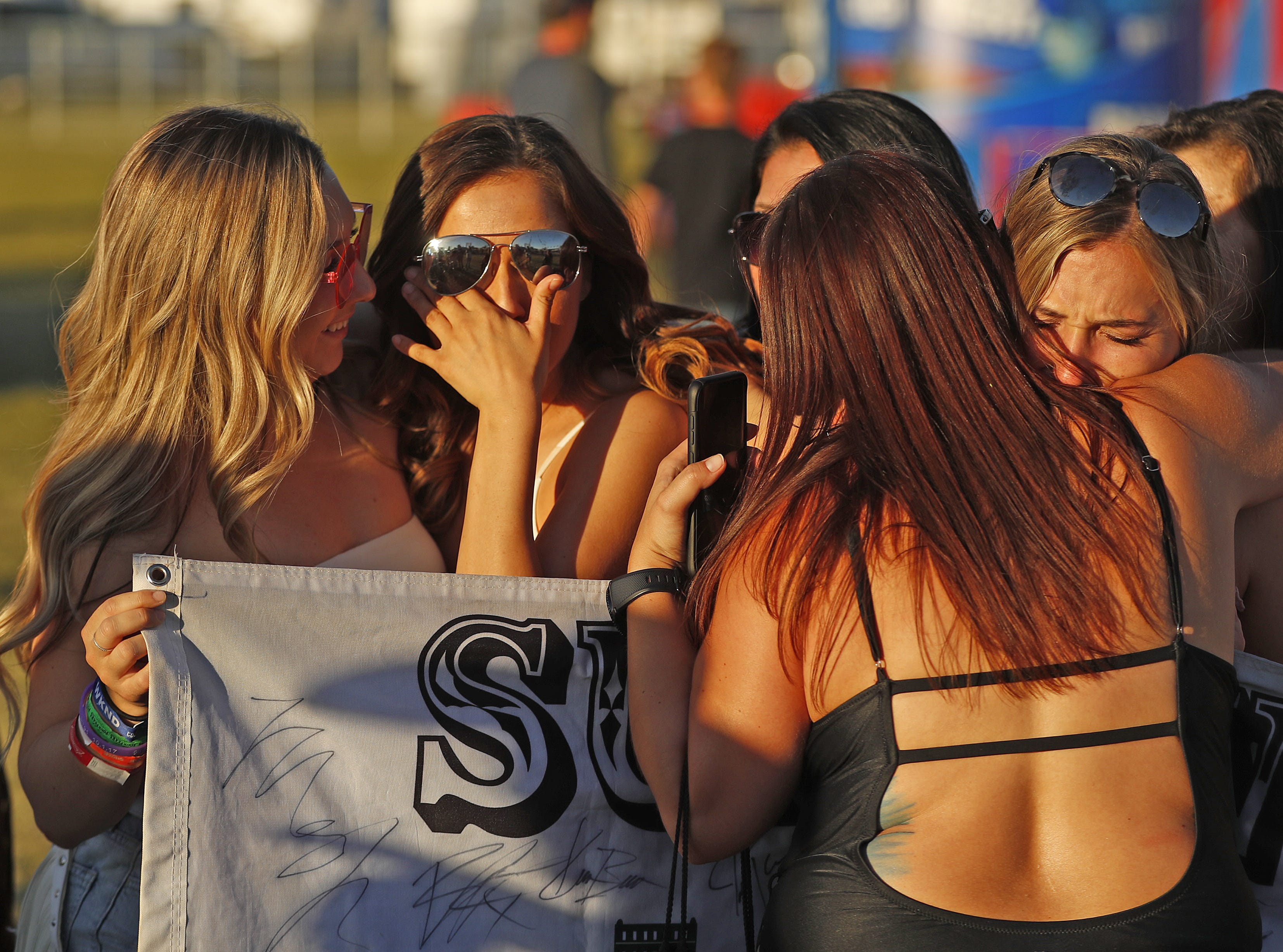 Kendall Alicata (left) holds Emily White as she cries while Kendall's sister Kalynn Alicata (right) receives a hug from another survivor of the Route 91 Harvest Festival shooting during Country Thunder in Florence, Arizona, on April 13, 2019.