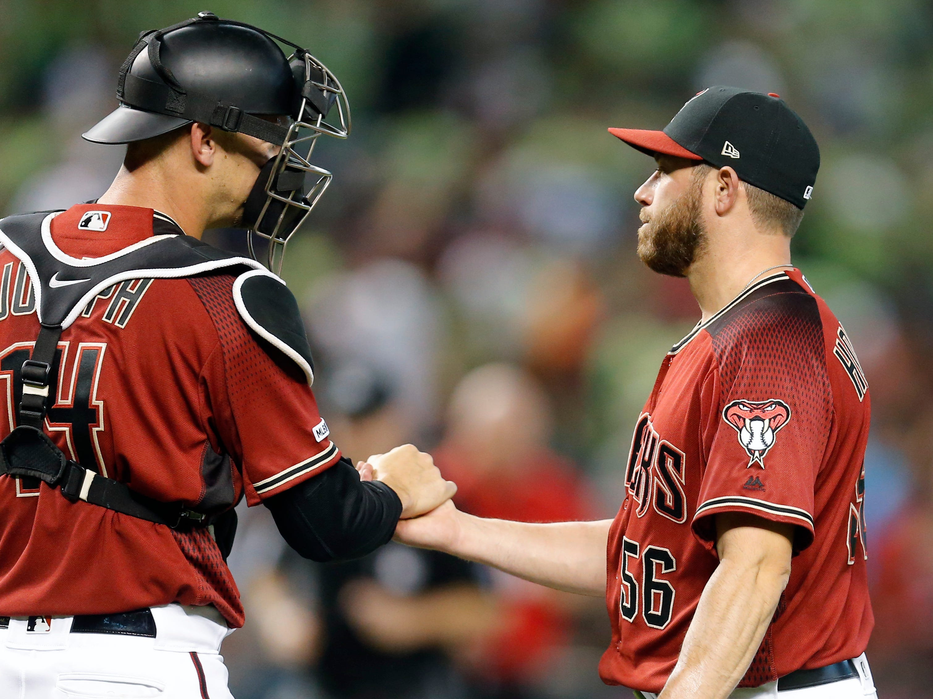 Arizona Diamondbacks pitcher Greg Holland (56) and Caleb Joseph celebrate after defeating the San Diego Padres during a baseball game, Sunday, April 14, 2019, in Phoenix. (AP Photo/Rick Scuteri)