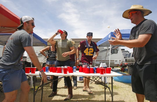 Clayton Boer (left) throws toward his teammate Ryan O'Halloran (right) while they play a drinking game against Austin Cooper (back left) and Nick Dunteman during Country Thunder in Florence, Ariz. on Sunday, April 14, 2019.