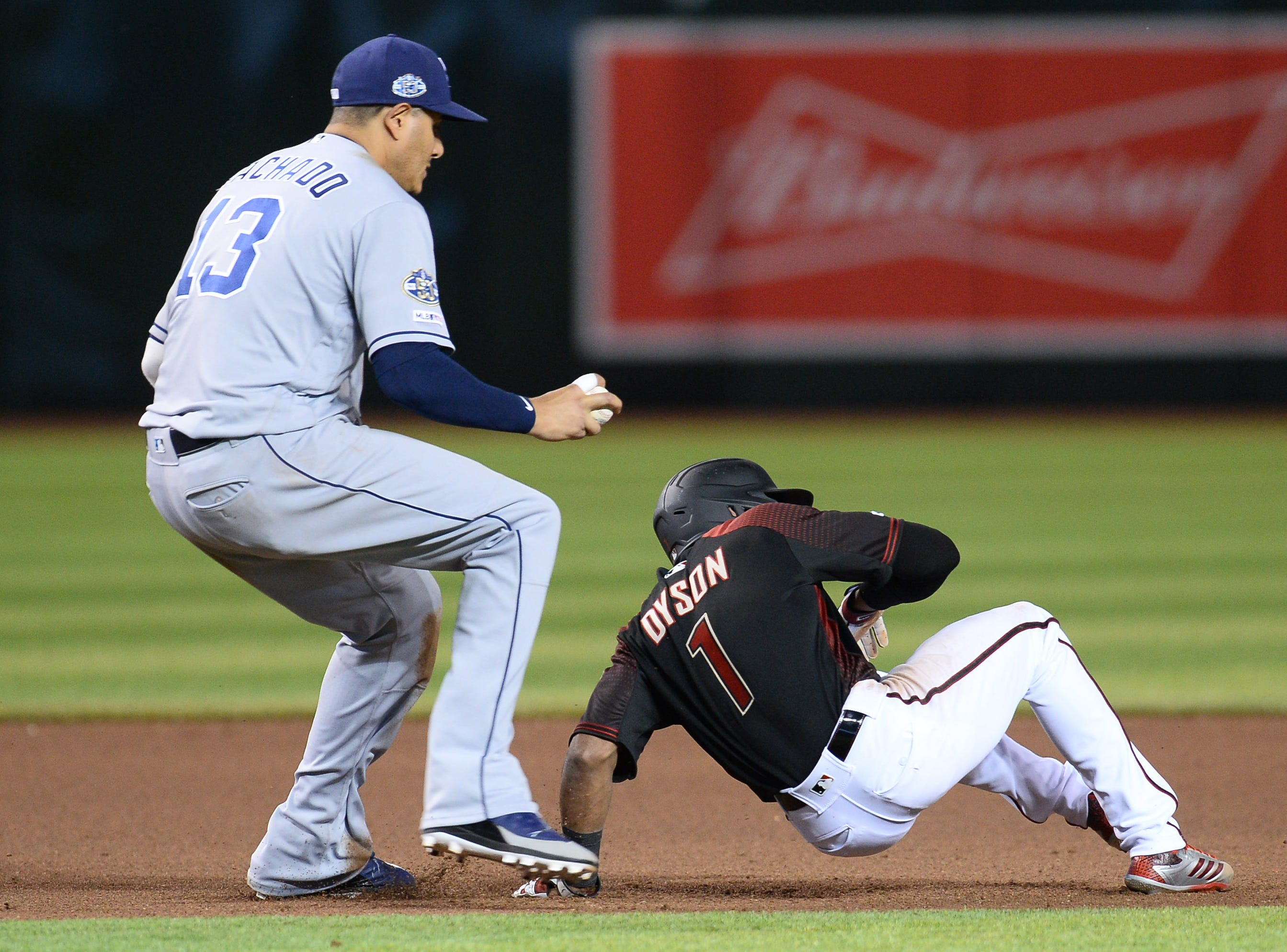 Apr 13, 2019; Phoenix, AZ, USA; San Diego Padres shortstop Manny Machado (13) tags out Arizona Diamondbacks center fielder Jarrod Dyson (1) during a run down during the seventh inning at Chase Field. Mandatory Credit: Joe Camporeale-USA TODAY Sports