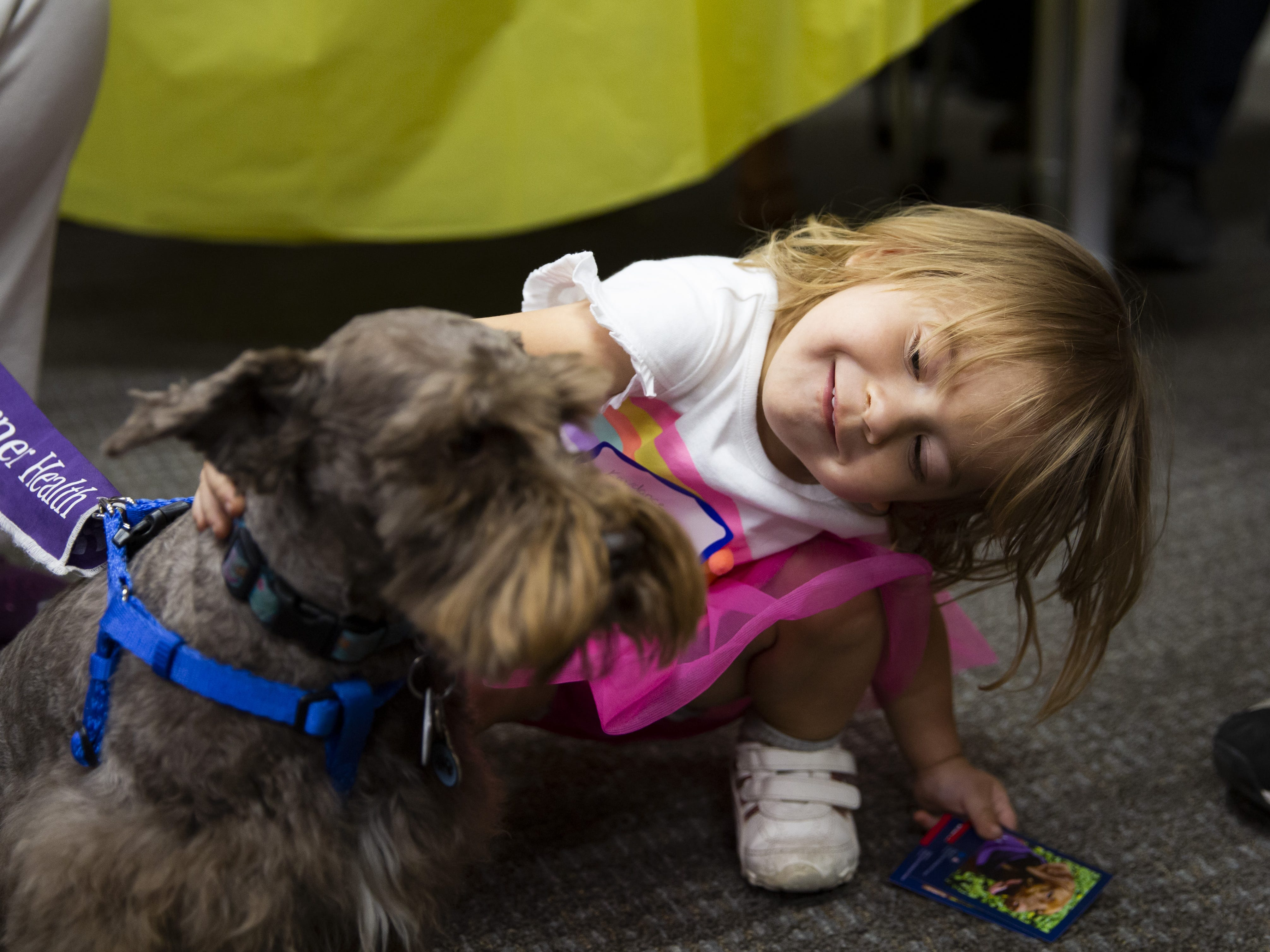 Kaydance Grimes, 2, pets a dog during the Preemie NICU Reunion at Banner University Medical Center on April 13, 2019.