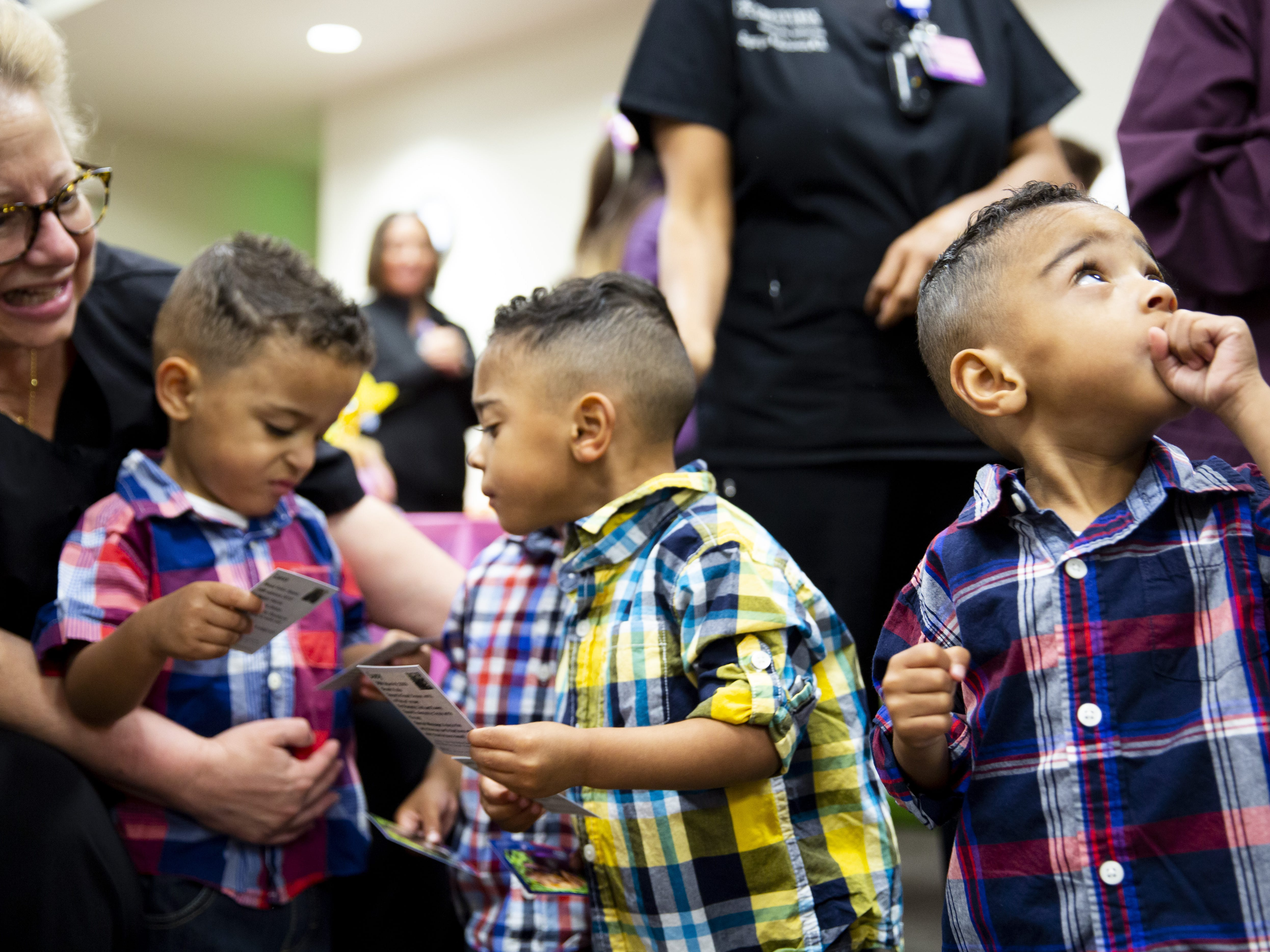 Isaiah, Liam and Jayden Craig look at dogs' business cards at the Preemie NICU Reunion at Banner University Medical Center on April 13, 2019. The boys are part of a set of quadruplets who were delivered at the University, and will turn three this May.