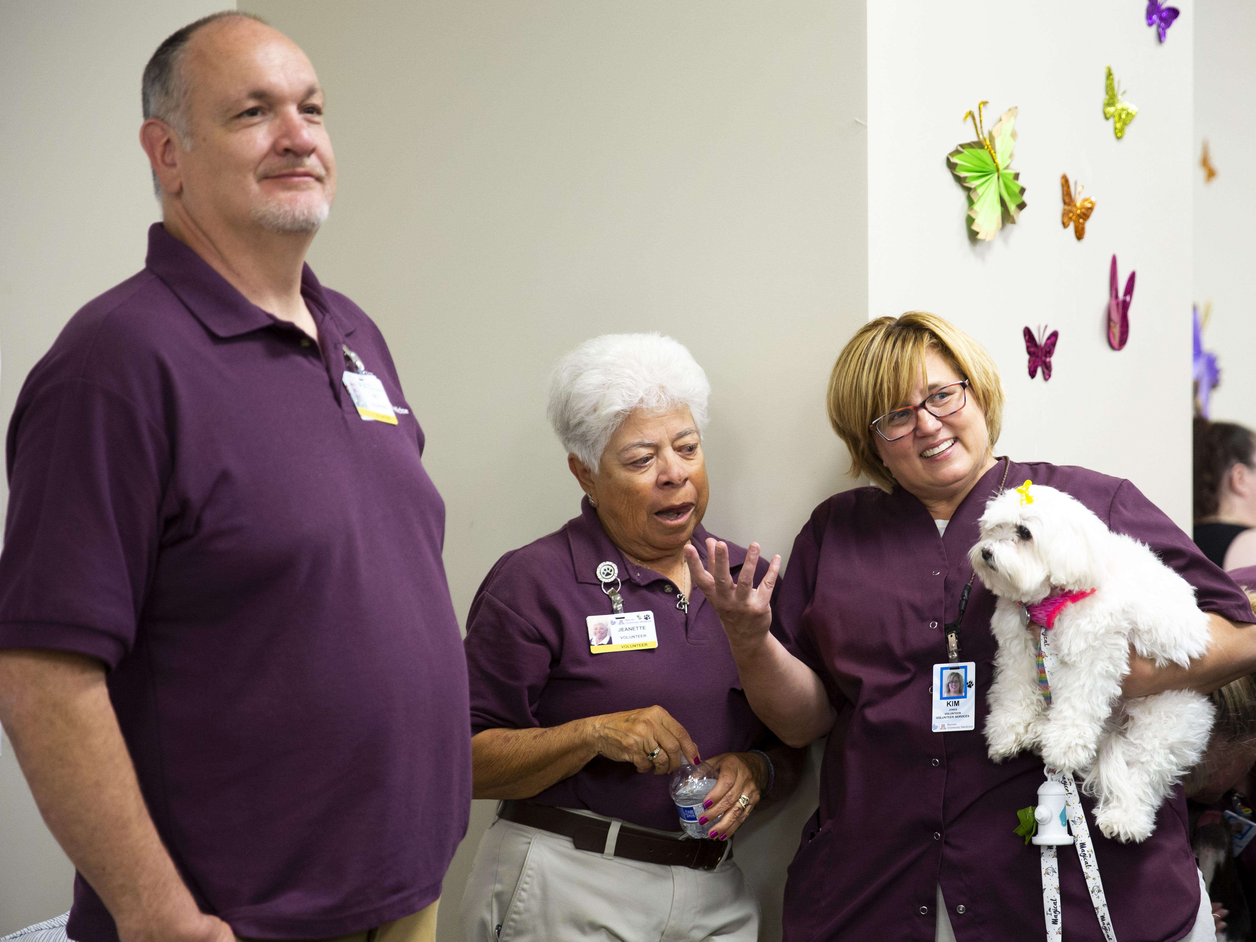 From left, Joe Jones, Jeanette Sinohui and Kim Jones talk together at the Preemie NICU Reunion at Banner University Medical Center on April 13, 2019. The three are in charge of some of the dogs that came to the reunion.