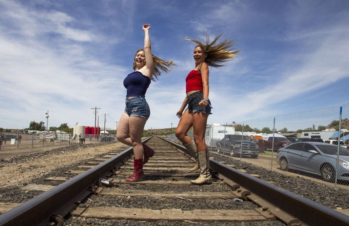 On the last day of Country Thunder Arizona, Morgan Eaton and Karlee Brown of Tempe dance on the railroad tracks Sunday, April 14, 2019, in Florence, Arizona.