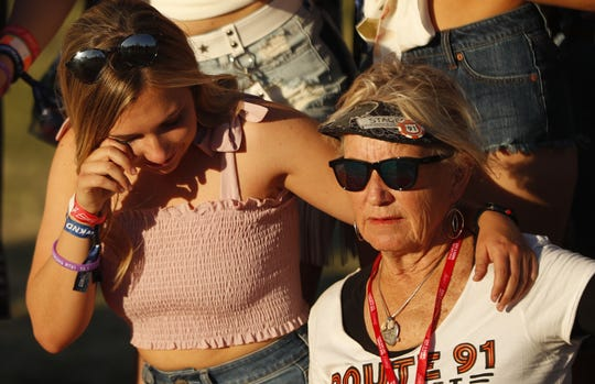 Kalynn Alicata wipes a tear as she puts her arm around Sue Nelson as tjeu take photos with survivors of the Route 91 Harvest Festival shooting during Country Thunder in Florence, Arizona, on April 13, 2019.