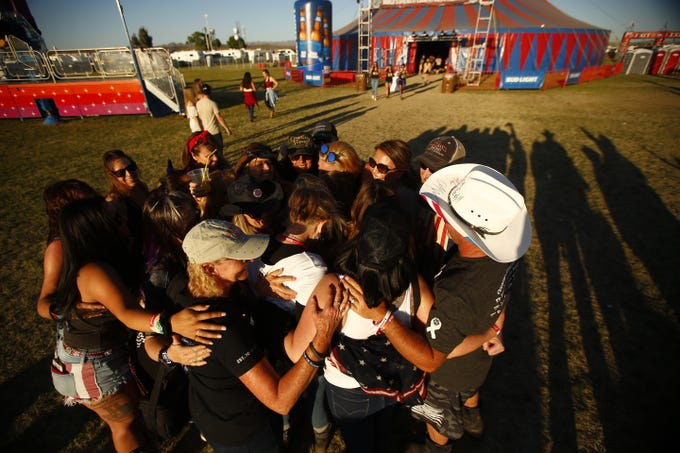 Survivors of the Route 91 Harvest Festival shooting in Las Vegas come in for a group hug during Country Thunder in Florence, Arizona, on April 13, 2019.