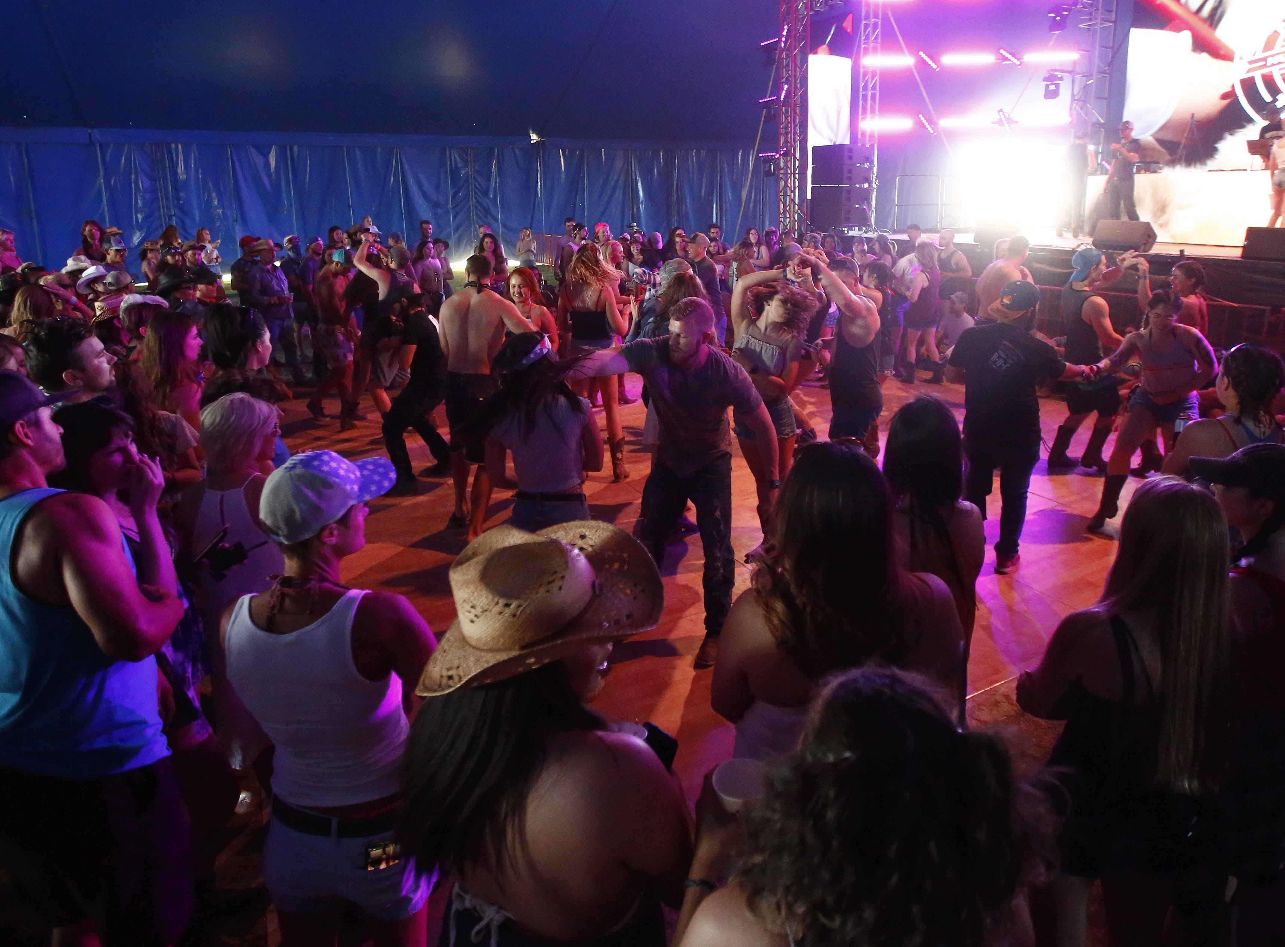 Contestants dance in an open time between rounds of Dancing with the Thunder competition inside the Electric Thunder tent during Country Thunder in Florence, Ariz. on Saturday, April 13, 2019.
