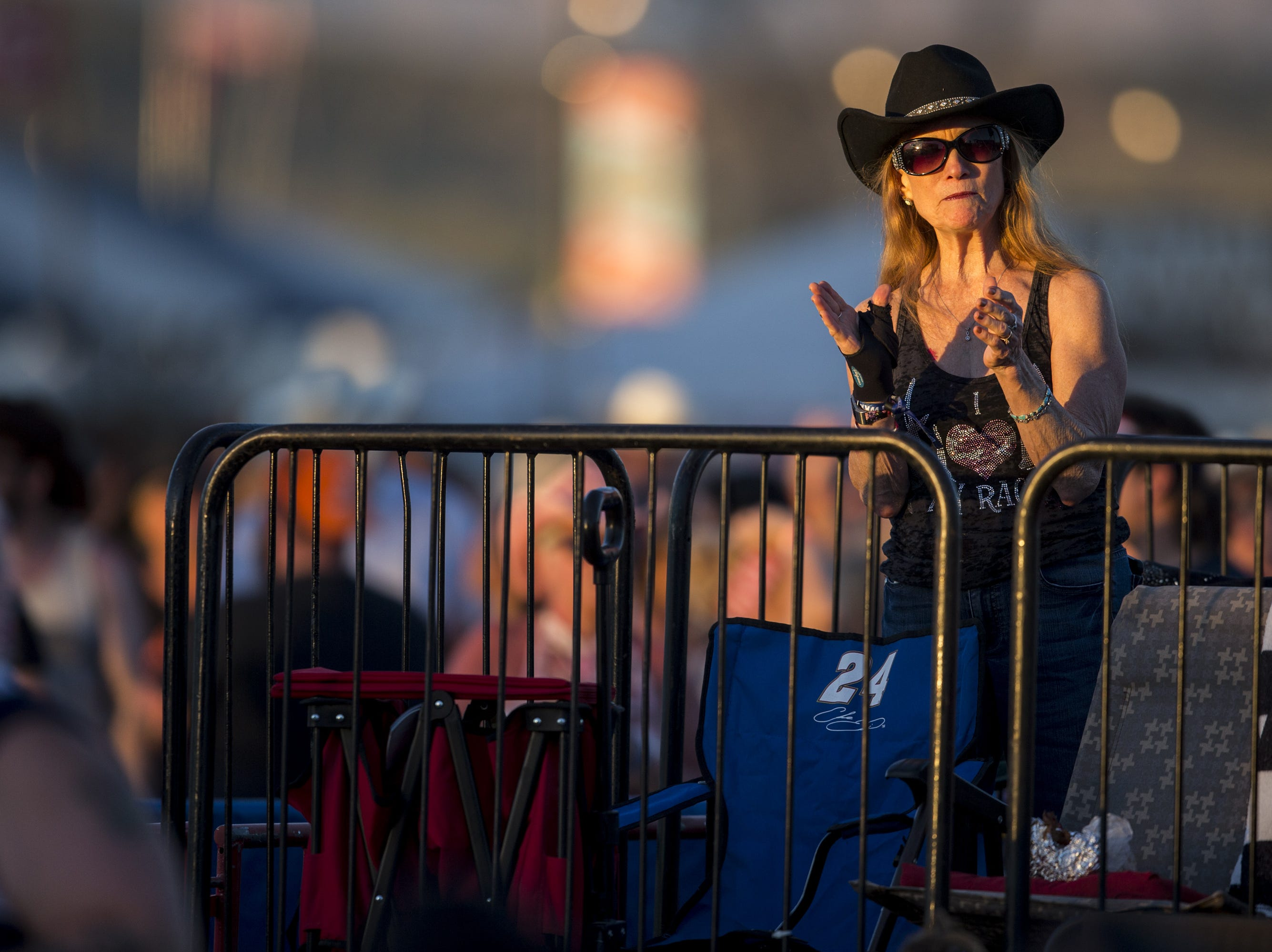 A fan watches Lonestar perform on Saturday, April 13, 2019, during Day 3 of Country Thunder Arizona in Florence, Ariz.