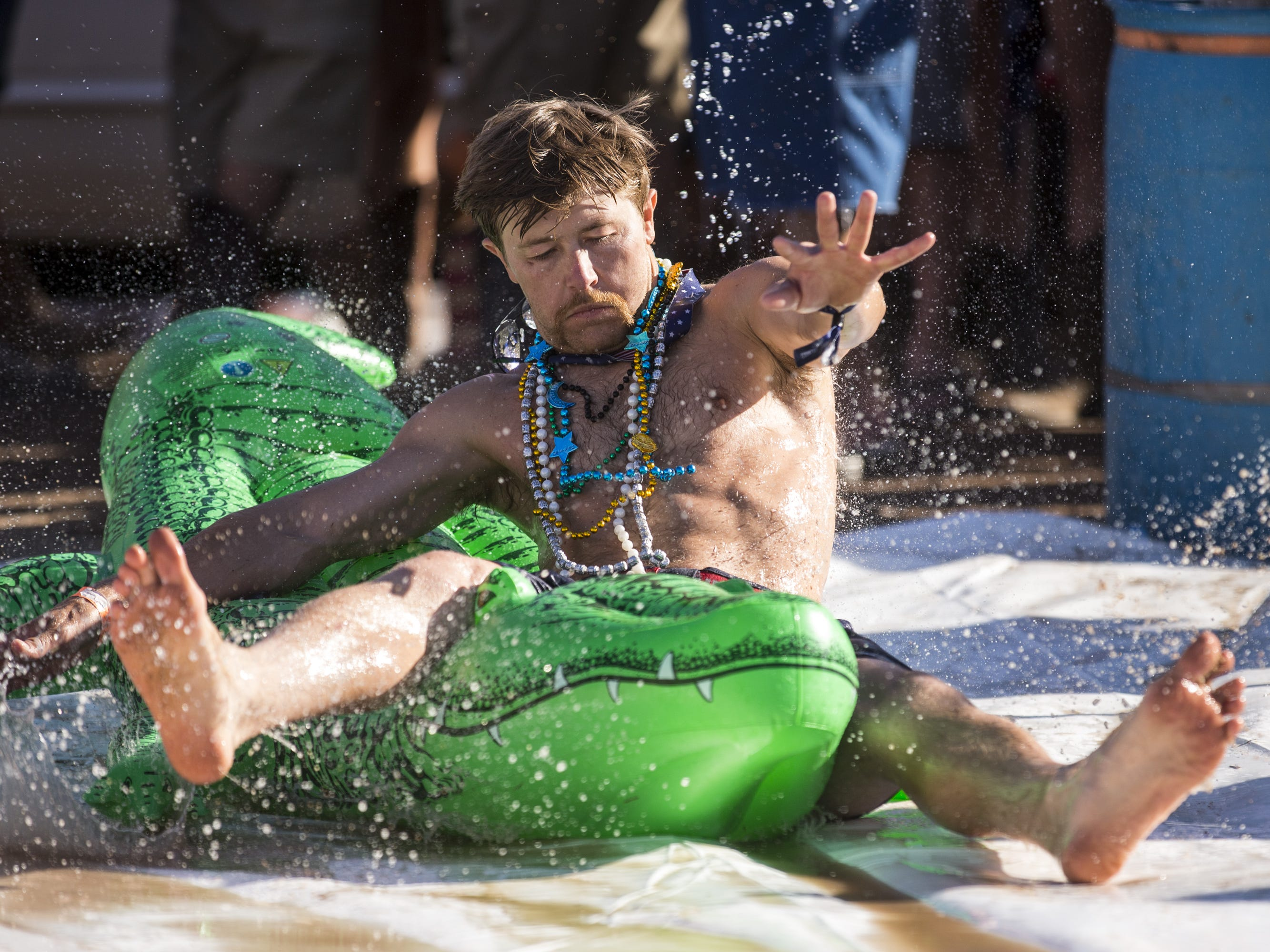 Dylan McGuire does a slip and slide at the Crazy Coyote campground on Saturday, April 13, 2019, during Day 3 of Country Thunder Arizona in Florence, Ariz.