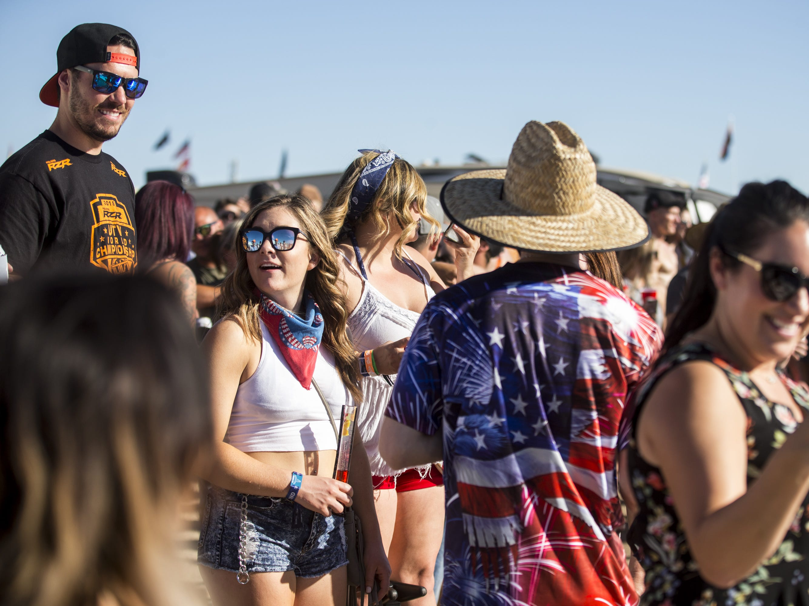 Festivalgoers watch people do a slip and slide on Saturday, Apr. 13, 2019, during Day 3 of Country Thunder Arizona in Florence, Ariz.