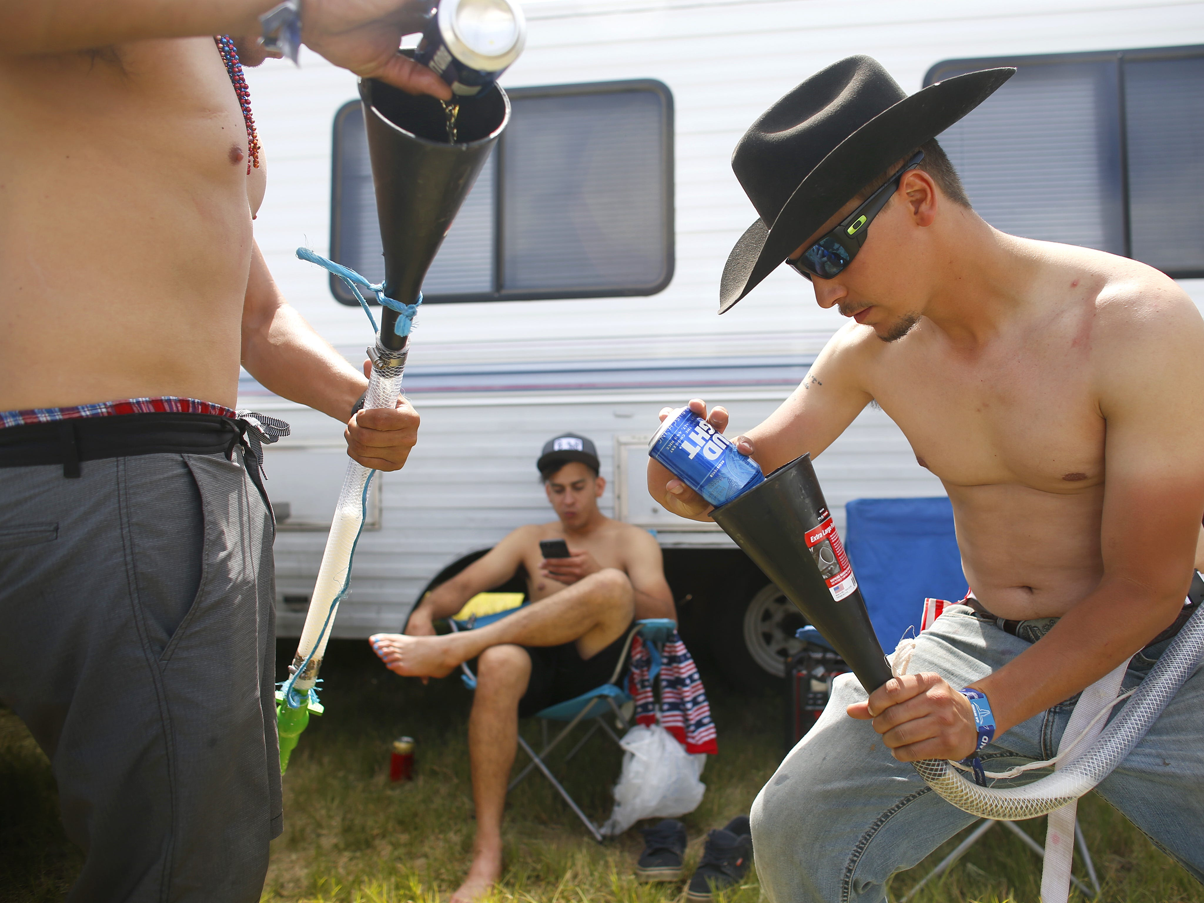 Max Pena (right) and his friend Brian Schurz (left) pour Bud Light into their beer bongs as Kenny Ramos watches during Country Thunder in Florence, Ariz. on Sunday, April 14, 2019.