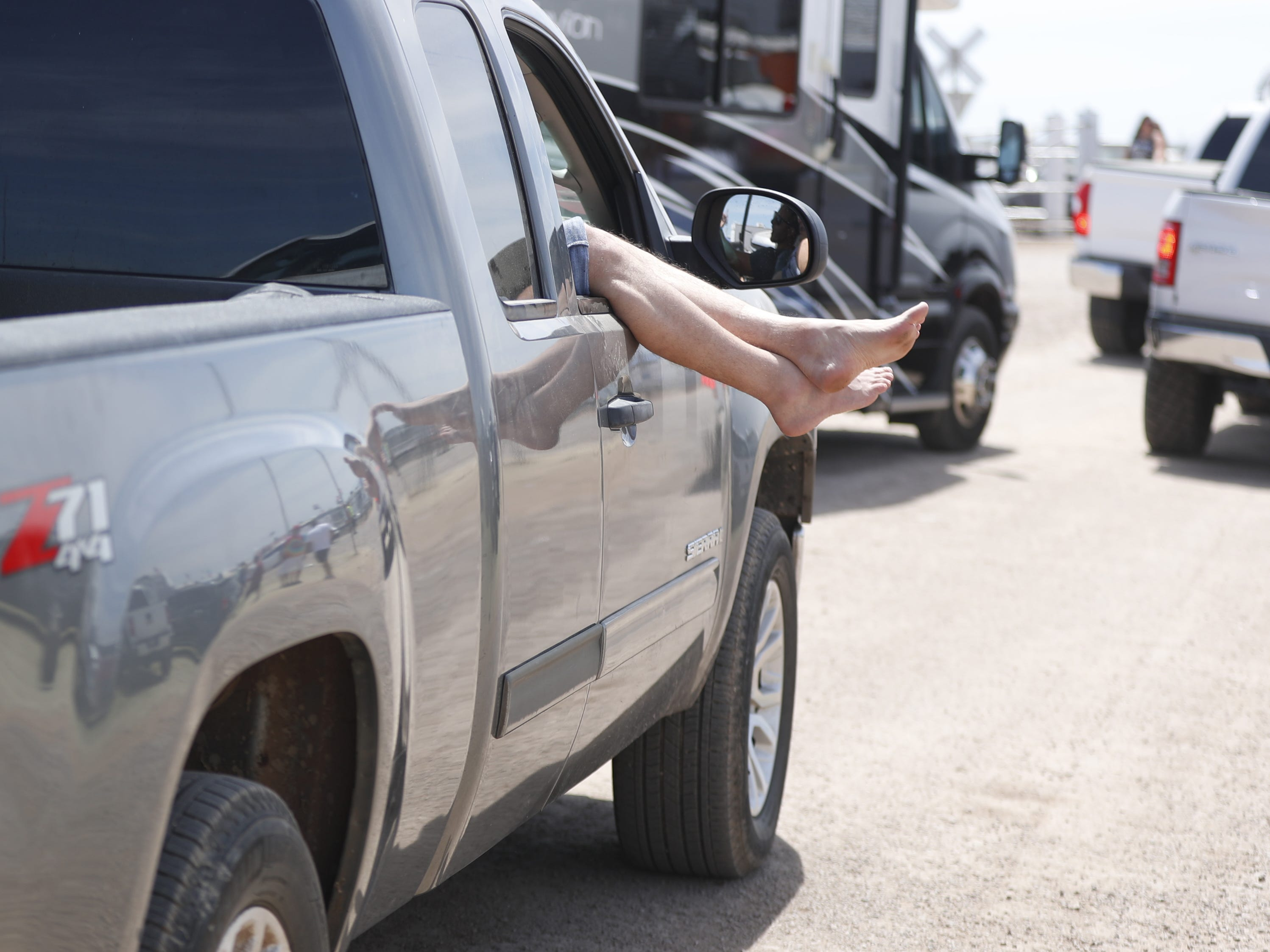 Feet stick out from a car window as people wait to leave during Country Thunder in Florence, Ariz. on Sunday, April 14, 2019.