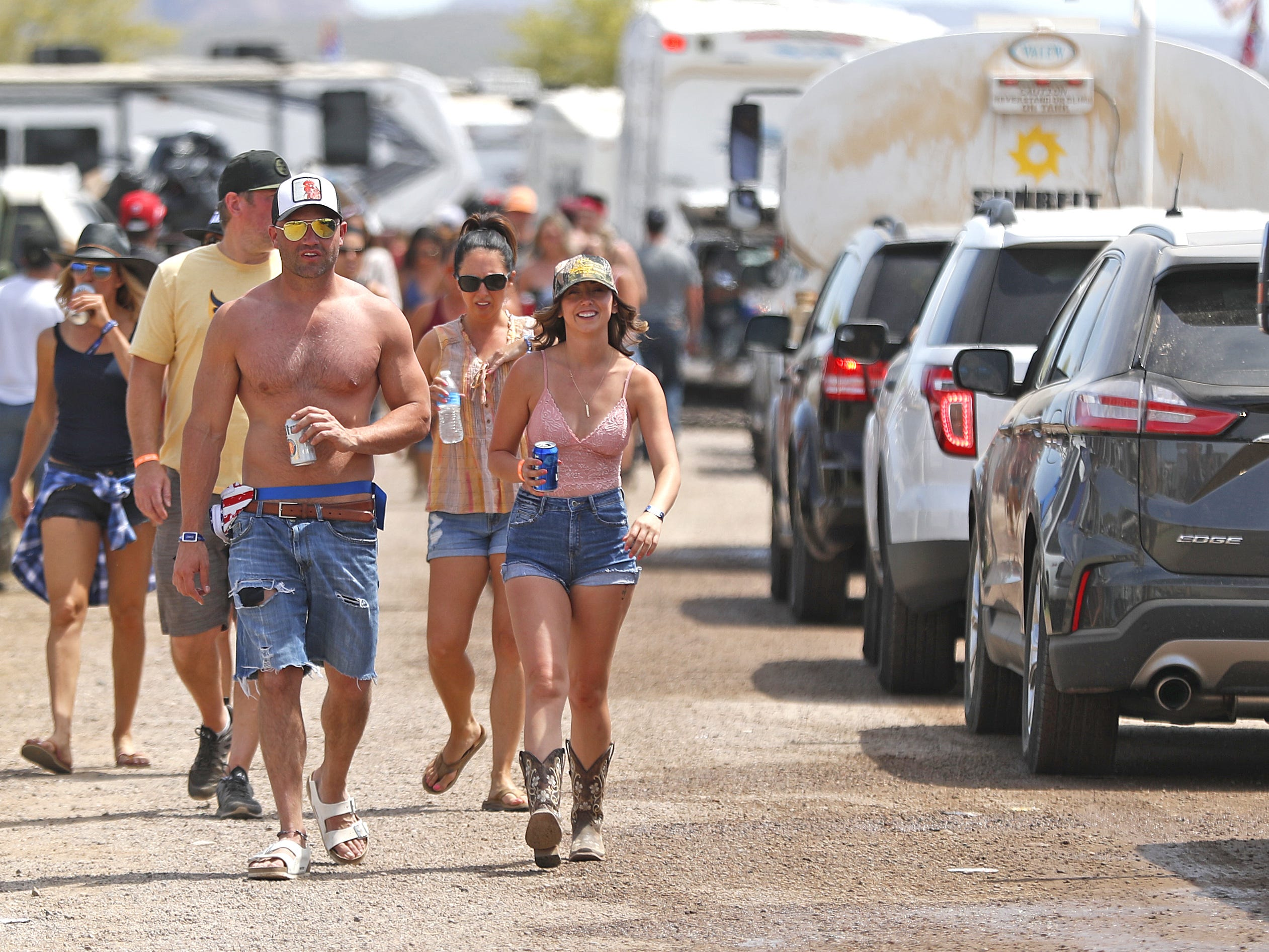 Country music fans walk the opposite direction as a line builds up of trucks and campers beginning to exit in the morning during Country Thunder in Florence, Ariz. on Sunday, April 14, 2019.