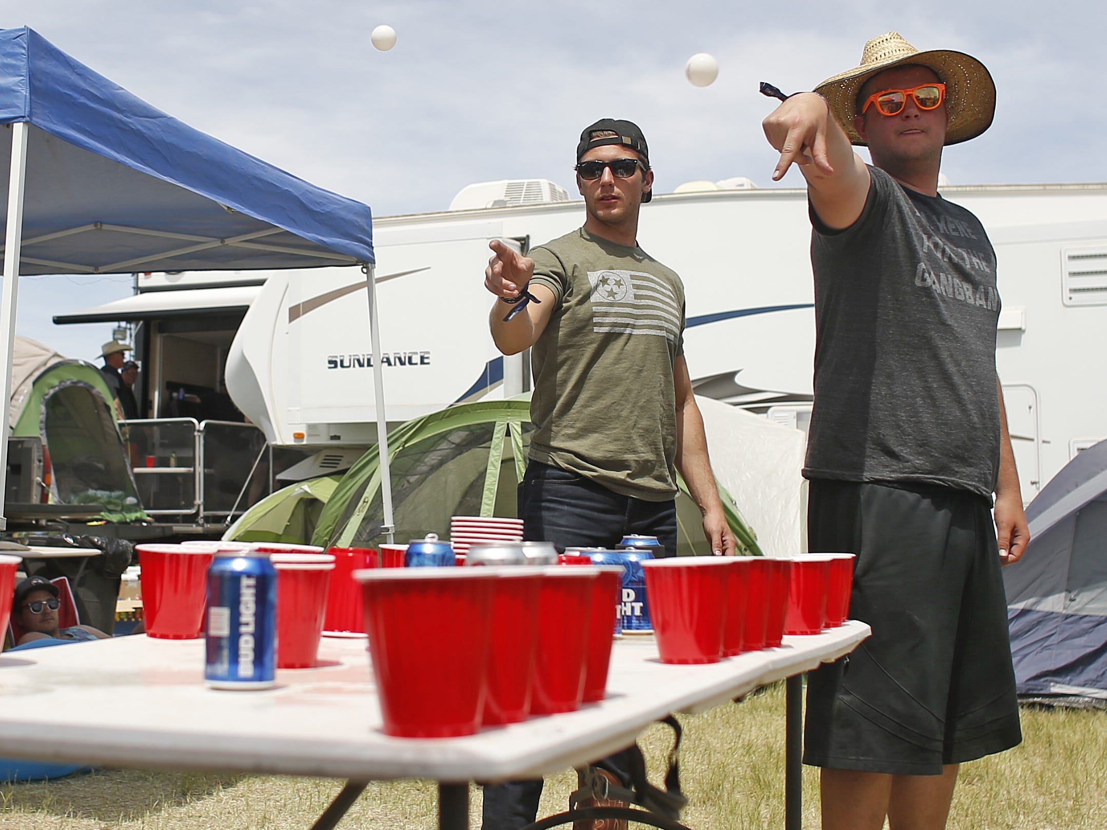 "Ryan O'Halloran, ""Papa Grande,"" (right) throws off against Austin Cooper, ""Birthday Boy,"" as the two play a drinking game called Dirt Cup during Country Thunder in Florence, Ariz. on Sunday, April 14, 2019."