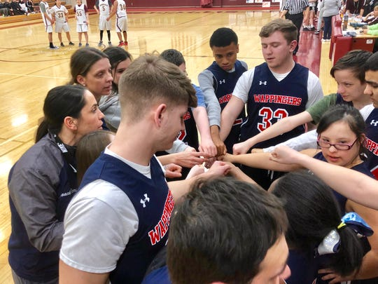 Wappingers unified basketball coaches Kerri Walsh and Kristen Perry huddle the team before its game against Arlington High School on Friday.