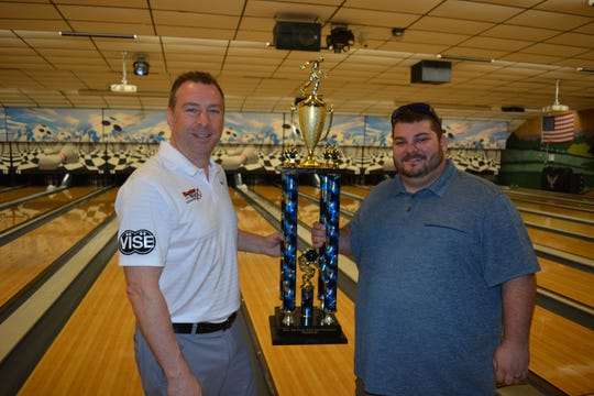 "Richard ""Ritchie"" Wolfe, left, accepts the BowlerMaxx York County Match Play Championship trophy from Sean Lemmon, manager of Laser Alleys, right.  Wolfe also won $1,000 for his victory."