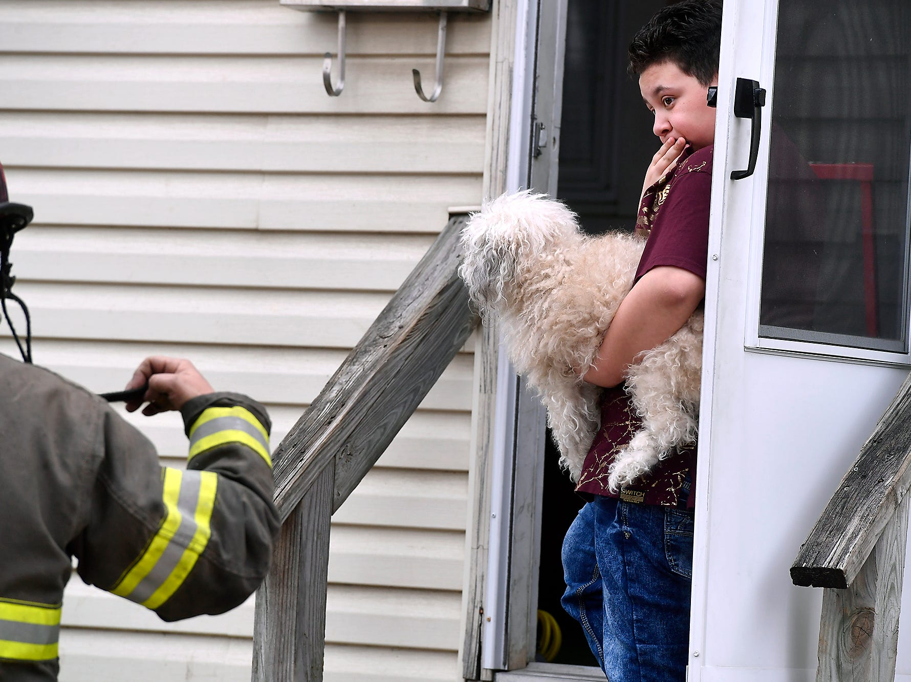 A boy holds the family doge while watching firefighters clear his home in the 600 block of S. Pershing Ave. of smoke after a small fire, Sunday, April 14, 2019. The fire was contained to a first floor laundry room. 