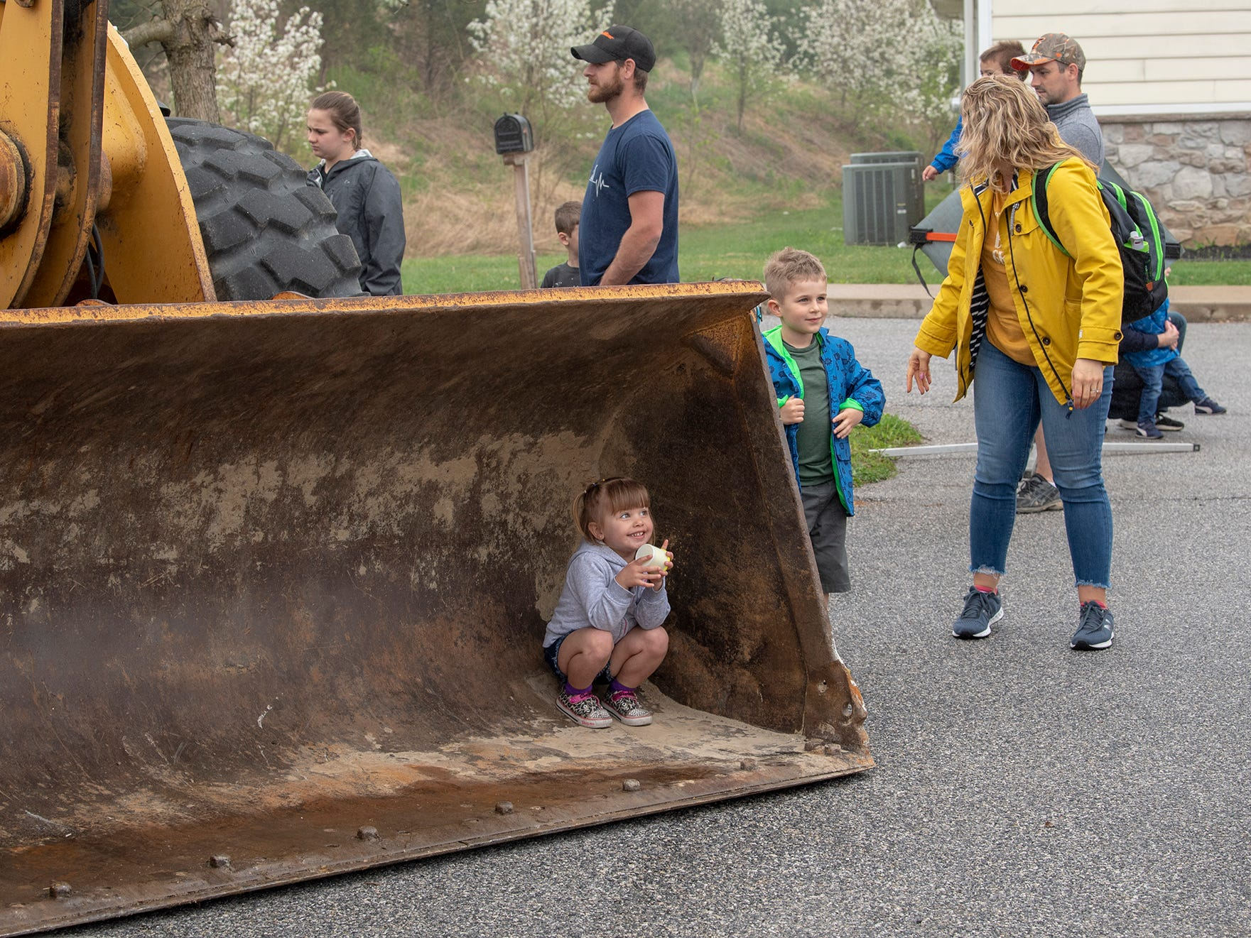 A child hunkers down inside the bucket of an excavator during a misty afternoon visiting the Truck Zoo at Paul Smith Library of Southern York County.