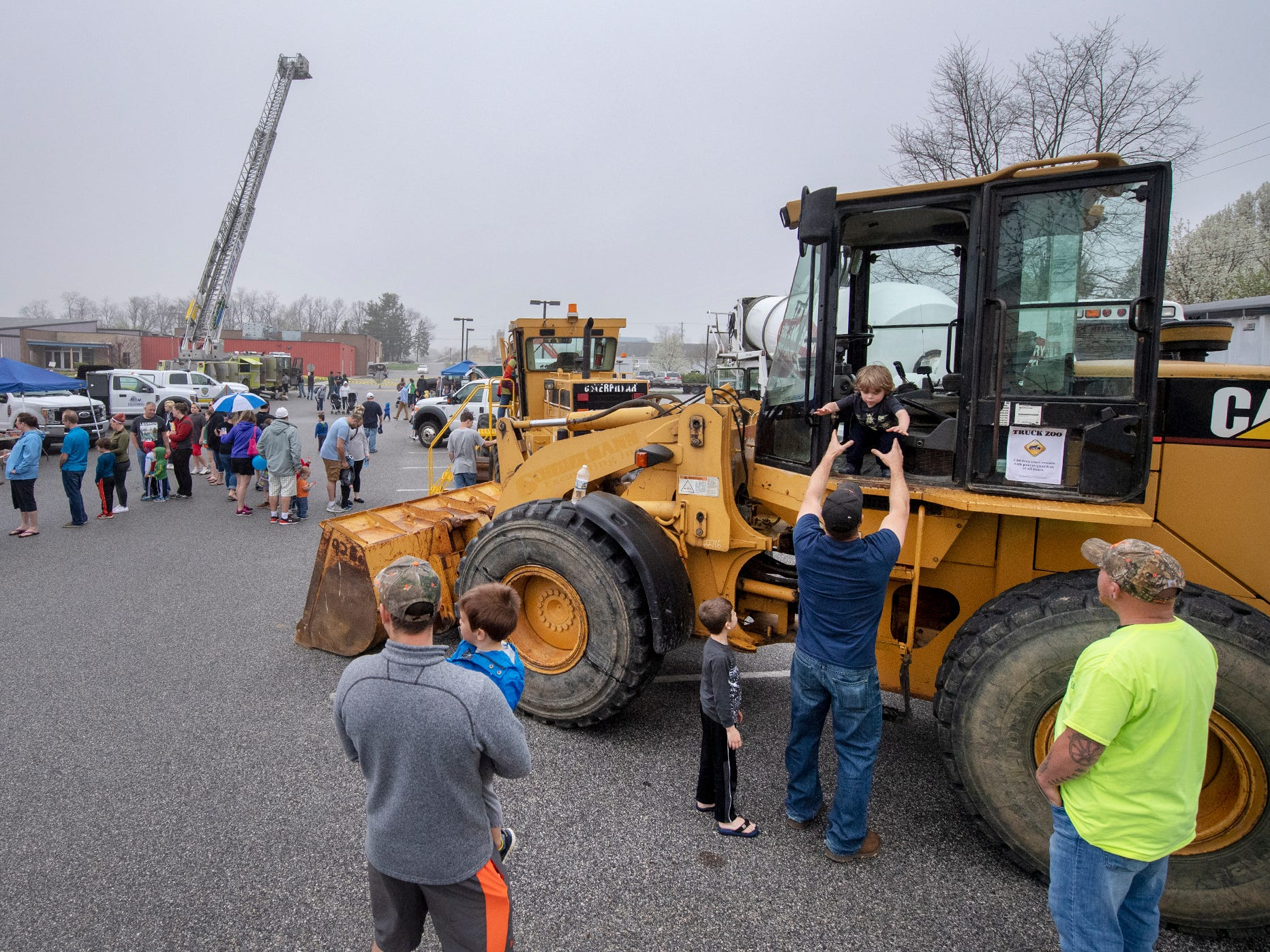 Children wait in lines for a chance to see a backhoe in action from the cab and get boosted into tall trucks during the Truck Zoo at Paul Smith Library of Southern York County.