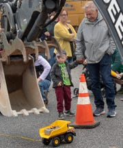 Caleb Simmons, 3, of Glen Rock, left, watches a backhoe demonstration with his grandfather Gary Whalen during the Truck Zoo at Paul Smith Library of Southern York County. The grandparents drove up from Delaware to bring their grandkids to the event.