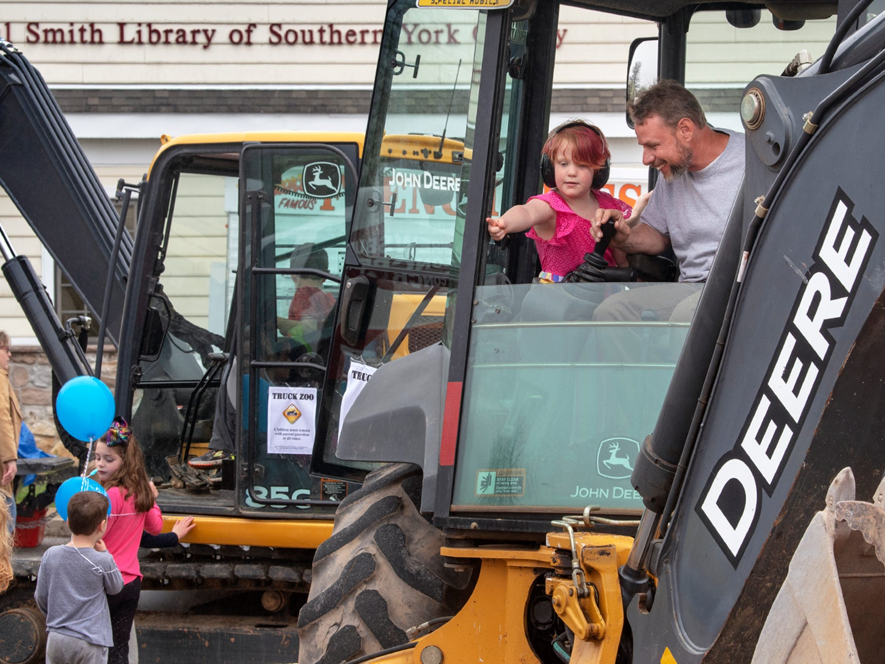 Dan Fiedler, right, of Clear View Excavating, Inc. lets Elliott Cunningham, age 4, of Felton direct the bucket of a backhoe during the Truck Zoo at Paul Smith Library of Southern York County. Equipment from six companies, two fire companies and Shrewsbury borough made their equipment available for children and parents to explore during the library's Big Book Sale fundraiser event Sunday April 14.